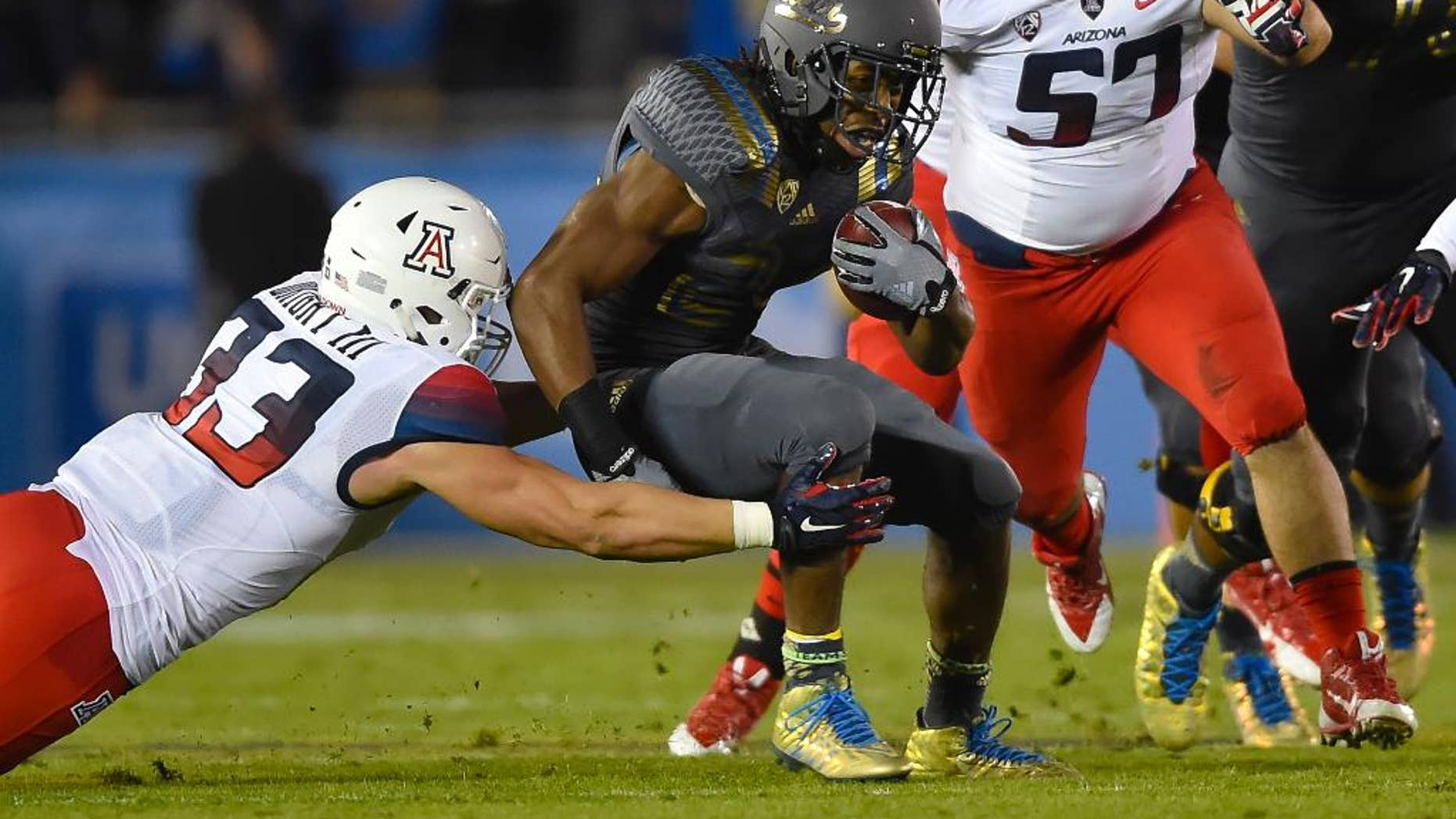 Arizona linebacker Scooby Wright III (33) and linebacker Cody Ippolito (57) close in on UCLA running back Paul Perkins, center, as he rushes during the first half of an NCAA college football game, Saturday, Nov. 1, 2014, in Pasadena, Calif. (AP Photo/Gus Ruelas)
