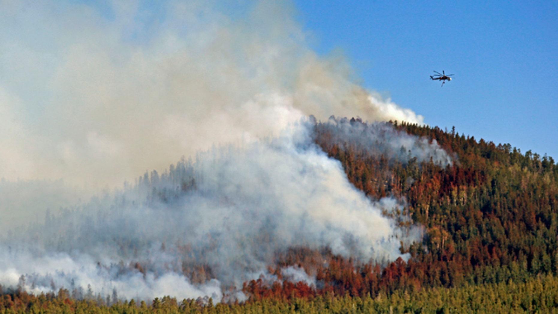 June 28, 2014: A helicopter hovers above the San Juan Fire in Vernon, Ariz.  (AP Photo/The Arizona Republic, David Kadlubowski)