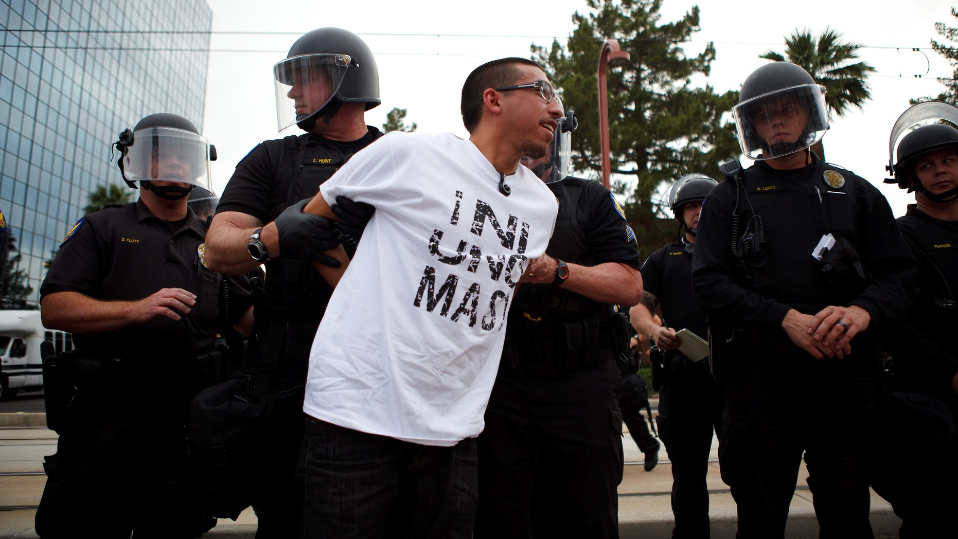 A protester opposed to SB 1070 is taken into custody by police officers April 25, 2012 in Phoenix, Arizona. (Photo by Jonathan Gibby/Getty Images)