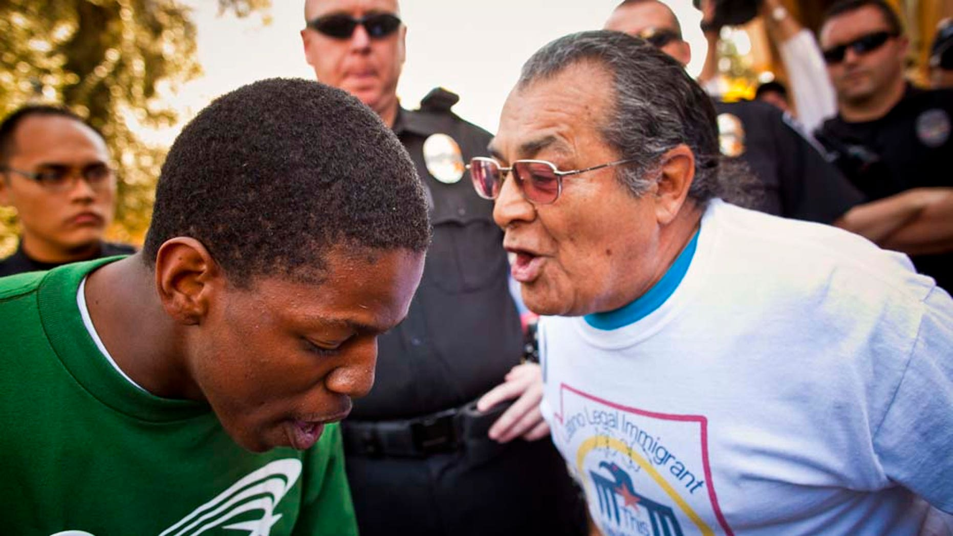 Jarvis Johnson, leftt, , a supporter of immigrants' rights and Arthur Olivas, right,  a supporter of Sen Russell Pearce's anti-immigrant bills, debate  at the State Capitol in Phoenix Tuesday, Feb. 22, 2011.   A sweeping bill that targets illegal immigrants in public housing, public benefits and the workplace drew vocal opposition Tuesday from Democrats.  The Senate Appropriations Committee was considering the 29-page bill Tuesday, a day after it was introduced by Republican Senate President Russell Pearce, who authored last year's controversial SB 1070. That law touched off a nationwide debate on whether states can enforce federal immigration laws. Democrats don't have the votes to block the measure, but the topic brought out supporters on both sides and security at the Senate was heightened, with about a dozen uniformed police officers deployed in and around the building. (AP Photo/The Arizona Republic, Jack Kurtz)