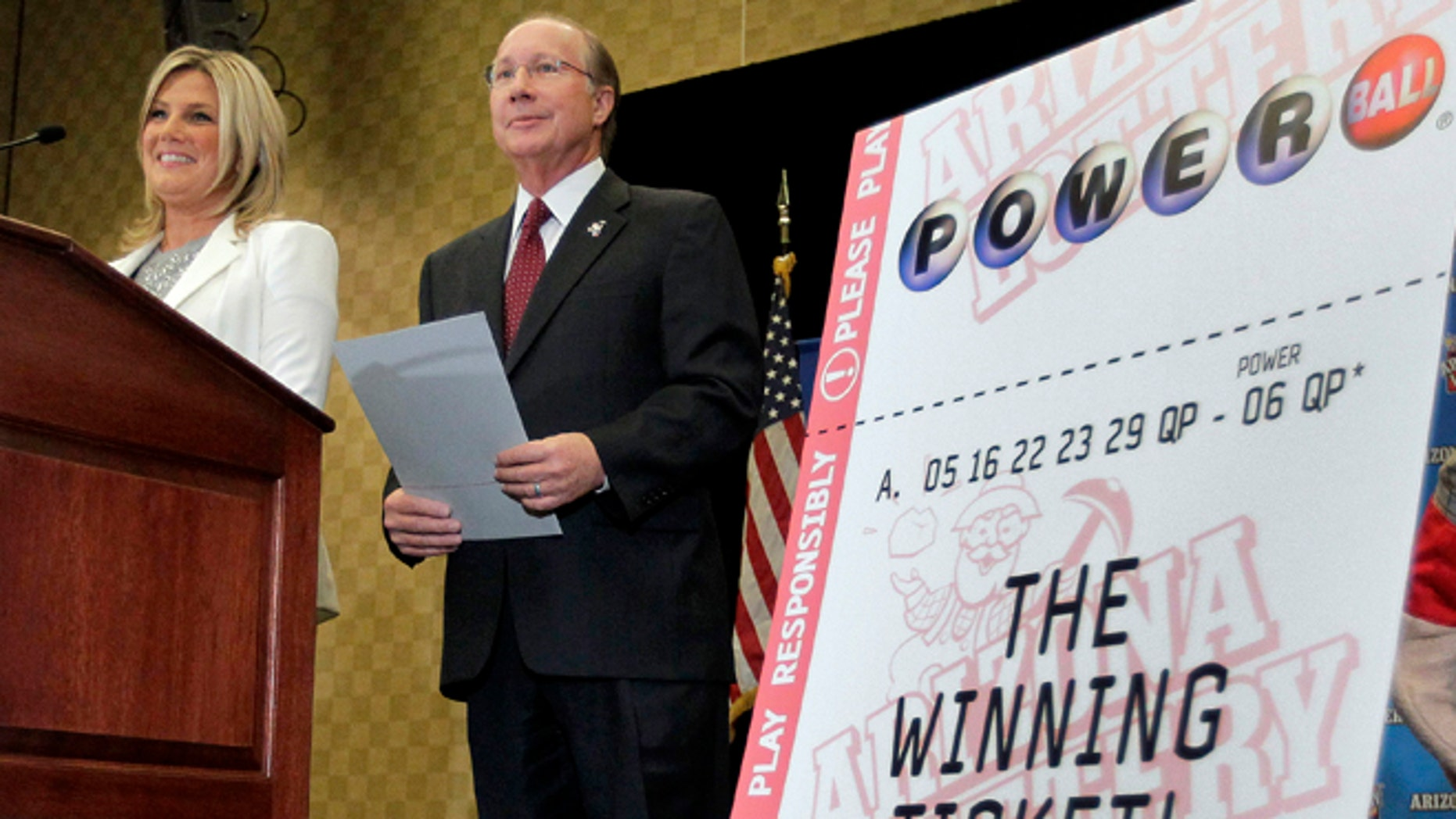 Dec. 7, 2012: Arizona Lottery Director of Budget, Products and Communications Karen Bach, left, and Arizona Lottery Executive Director Jeff Hatch-Miller stand next to an enlargement of the winning $587.5 Million Powerball ticket during a news conference in Scottsdale, Ariz.