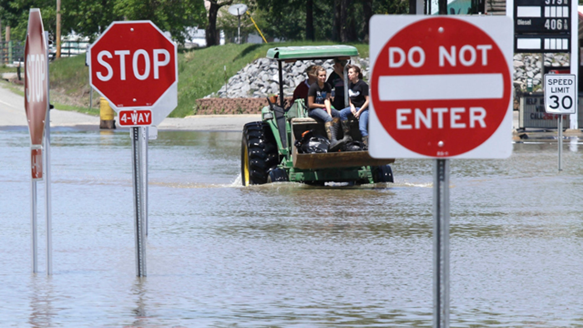 May 4: Two girls ride a tractor through a flooded intersection in Des Arc, Ark.