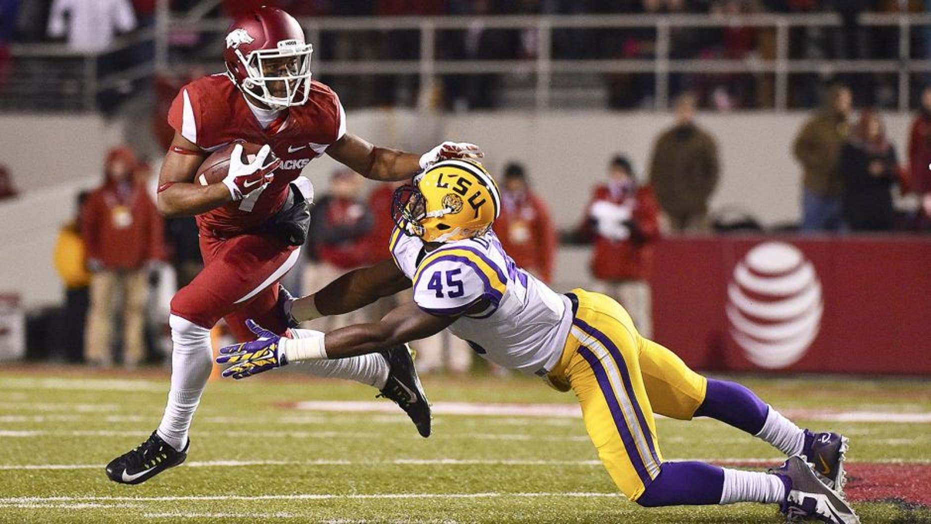 Nov 15, 2014; Fayetteville, AR, USA; Arkansas Razorbacks wide receiver Damon Mitchell (7) breaks the tackle of LSU Tigers linebacker Deion Jones (45) during the first half at Donald W. Reynolds Razorback Stadium. Mandatory Credit: Jasen Vinlove-USA TODAY Sports