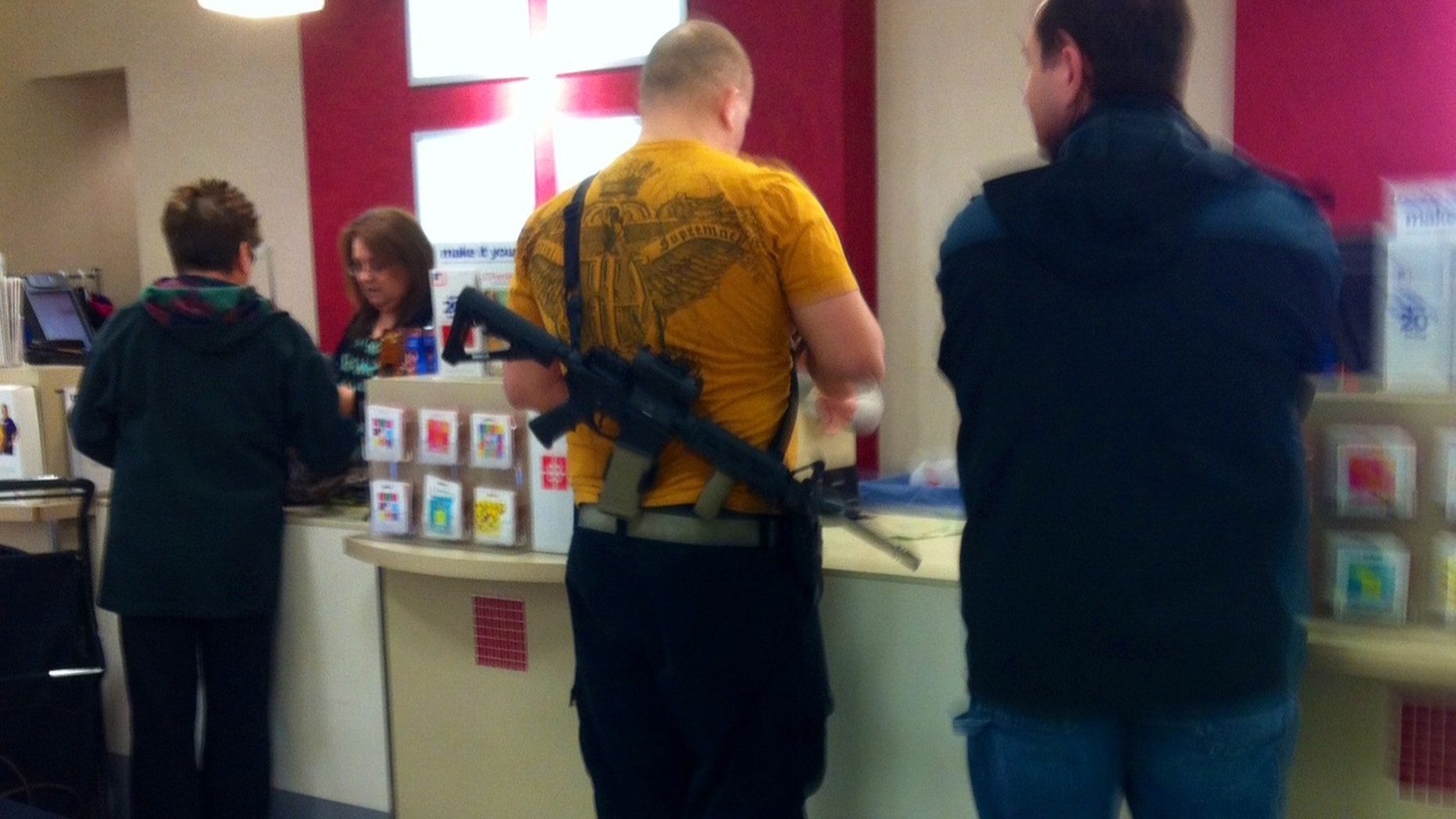 Jan. 13, 2013: This cell phone photo provided by Cindy Yorgason shows a JC Penney shopper with an assault rifle over his shoulder in Riverdale, Utah.