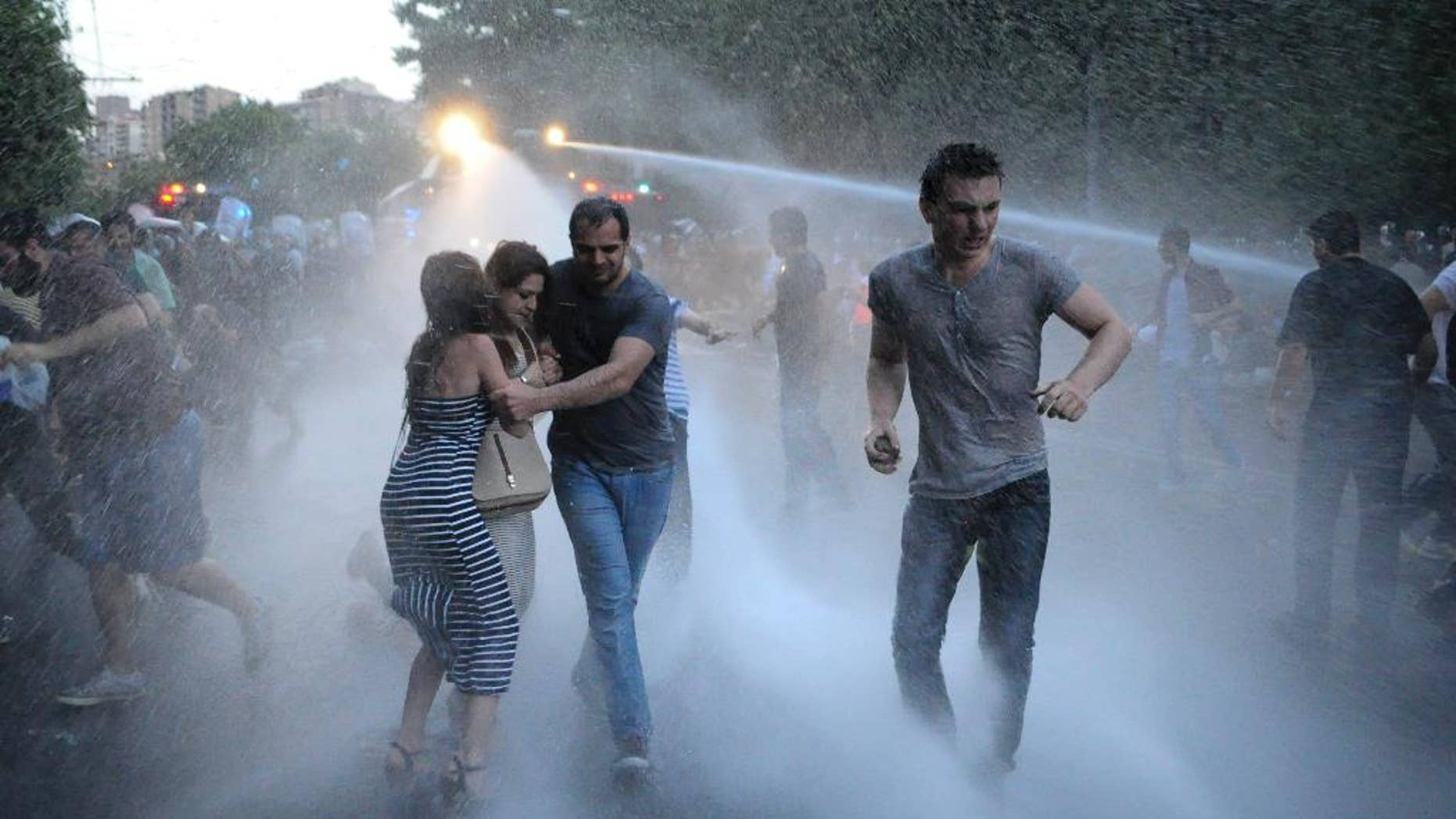 FILE - In this Tuesday, June 23, 2015, file photo, Armenian police use water cannons to disperse protesters demonstrating against an increase in electricity prices in the Armenian capital of Yerevan. The protests are continuing despite the president's decision to suspend the price rise. (Narek Aleksanyan/PAN Photo via AP, File