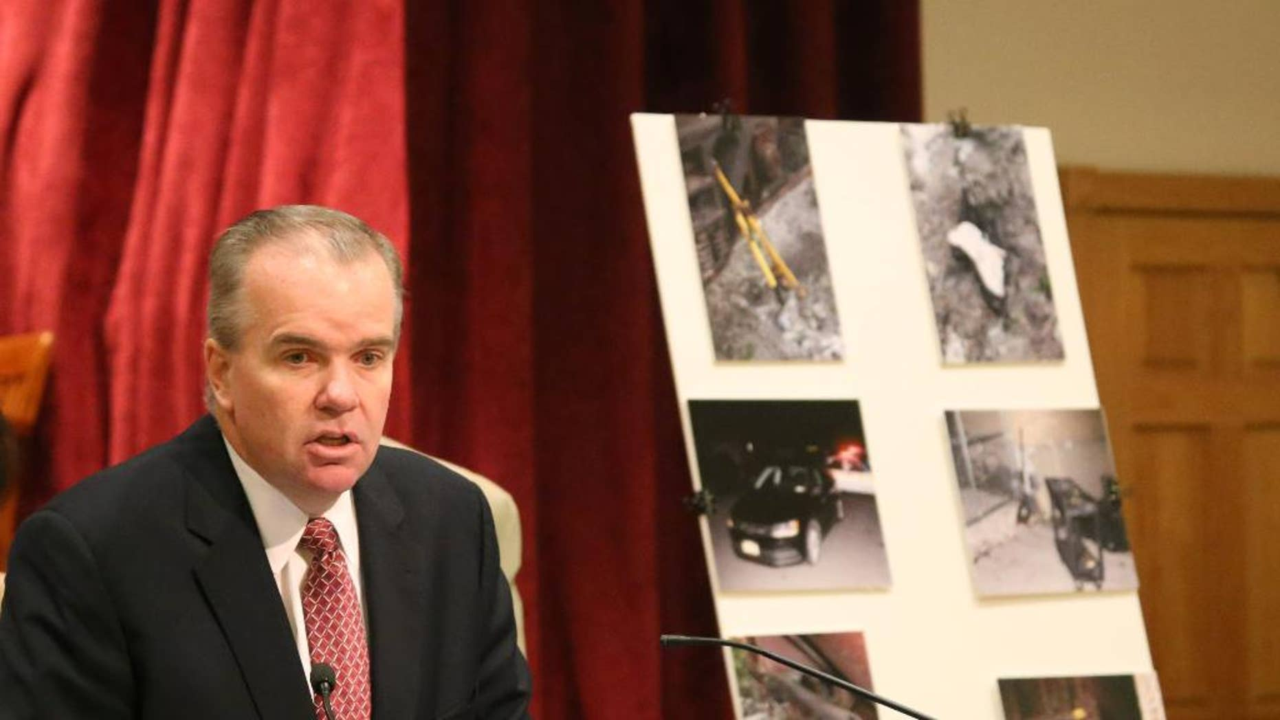 Acting Nassau County Police Commissioner Thomas Krumpter speaks with reporters on Aug. 27, 2015 in Mineola, N.Y., as he stands in front of a board showing crime scene photos of a botched burglary at an armored car company in Hicksville, N.Y. Authorities say a group of sophisticated burglars penetrated a vault of a Long Island armored car company and stole $1.8 million on Aug. 16, 2015, but were foiled by an alert police officer. (AP Photo/Mike Balsamo)