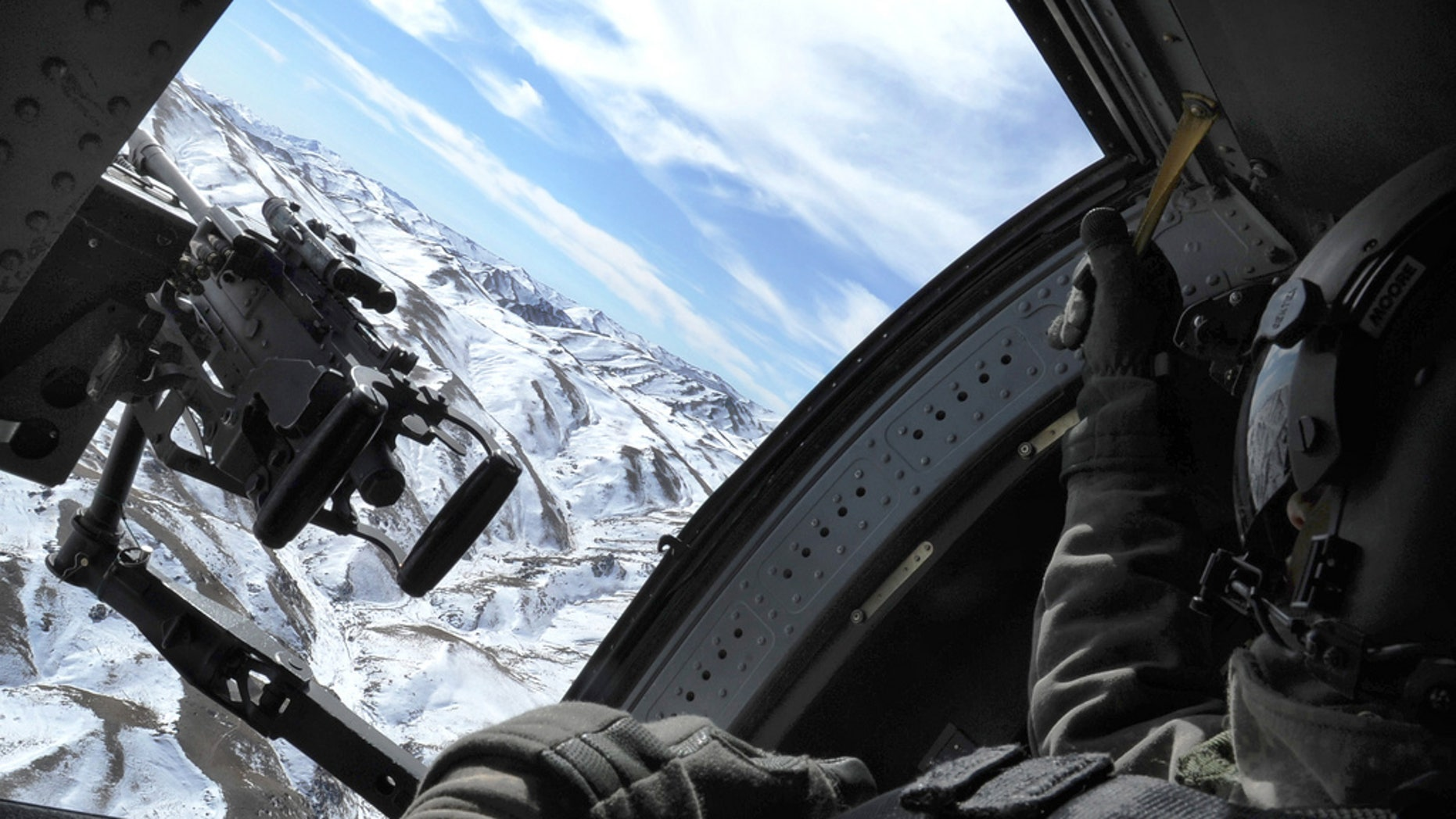 Specialist Kayla Moore covers her sector in a UH-60 Black Hawk while traveling from Forward Operating Base Lightning to Contingency Operating Base Ajiristan Afghanistan January 20, 2010. SPC Moore is a Black Hawk Crew Chief assigned to the A Company 2-3 Aviation Regiment in Support of Operation Enduring Freedom.