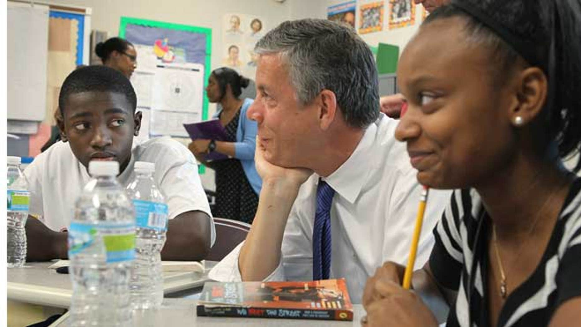 In this Monday, June 25, 2012 file photo, during a fact-finding tour of Vashon High School, U.S. Secretary of Education Arne Duncan, center, listens to eighth-grade students Delvion Mitchell, 14, and Makayla Lewis, 14, as they discuss social issues they have encountered at school and what they have learned from them, in St. Louis.