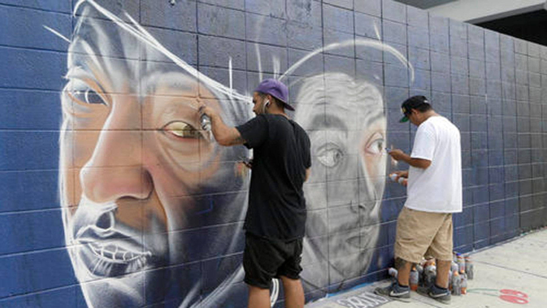 Artists Theo Magma, of Spain, left, and Koka, of Mexico, right, work on a mural, Friday, Dec. 2, 2016, in the Wynwood Art District in Miami, as the annual Art Basel festival continues, featuring poolside parties, blocks of art fairs and outdoor red carpet events. This marks the 15th year that Art Basel has been held in the Miami area. (AP Photo/Alan Diaz)