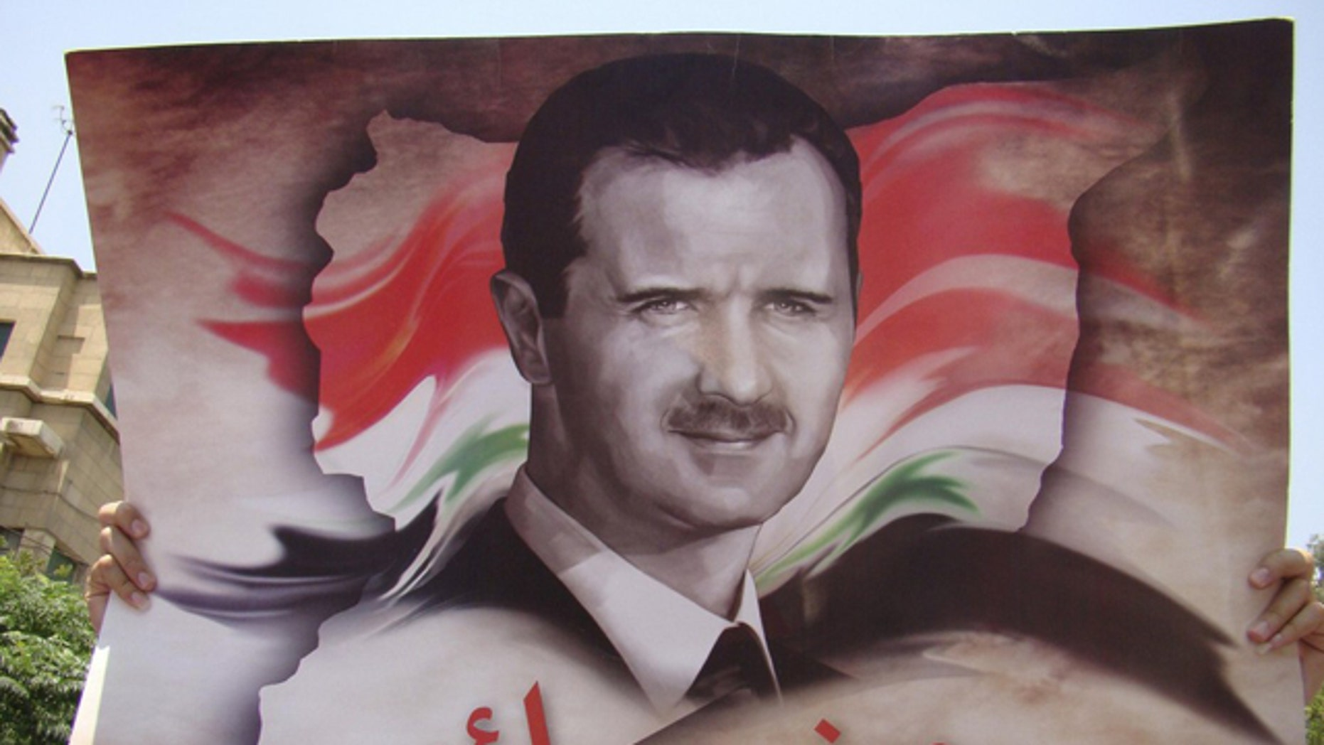 July 11: A government loyalists holds a picture of Syria's President Bashar al-Assad during a protest outside the U.S. embassy in Damascus.