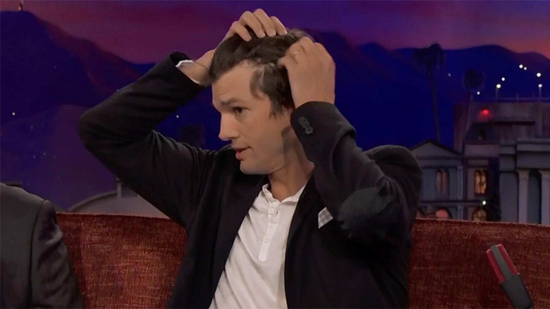 Ashton Kutcher revealed his receding hairline to TV host Conan O'Brien Monday night.
