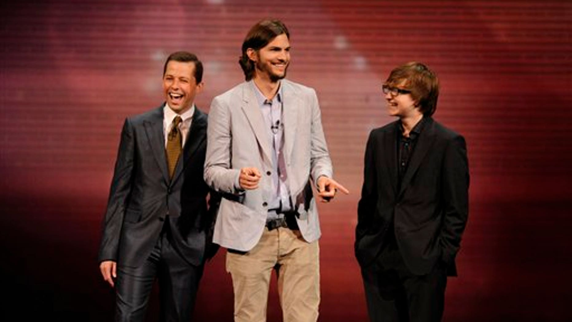 "In this May 18, 2011 file publicity image released by CBS, the cast of ""Two and a Half Men,"" from left, Jon Cryer, Ashton Kutcher, and Angus T. Jones are shown during their presentation at CBS' Upfronts (AP)"