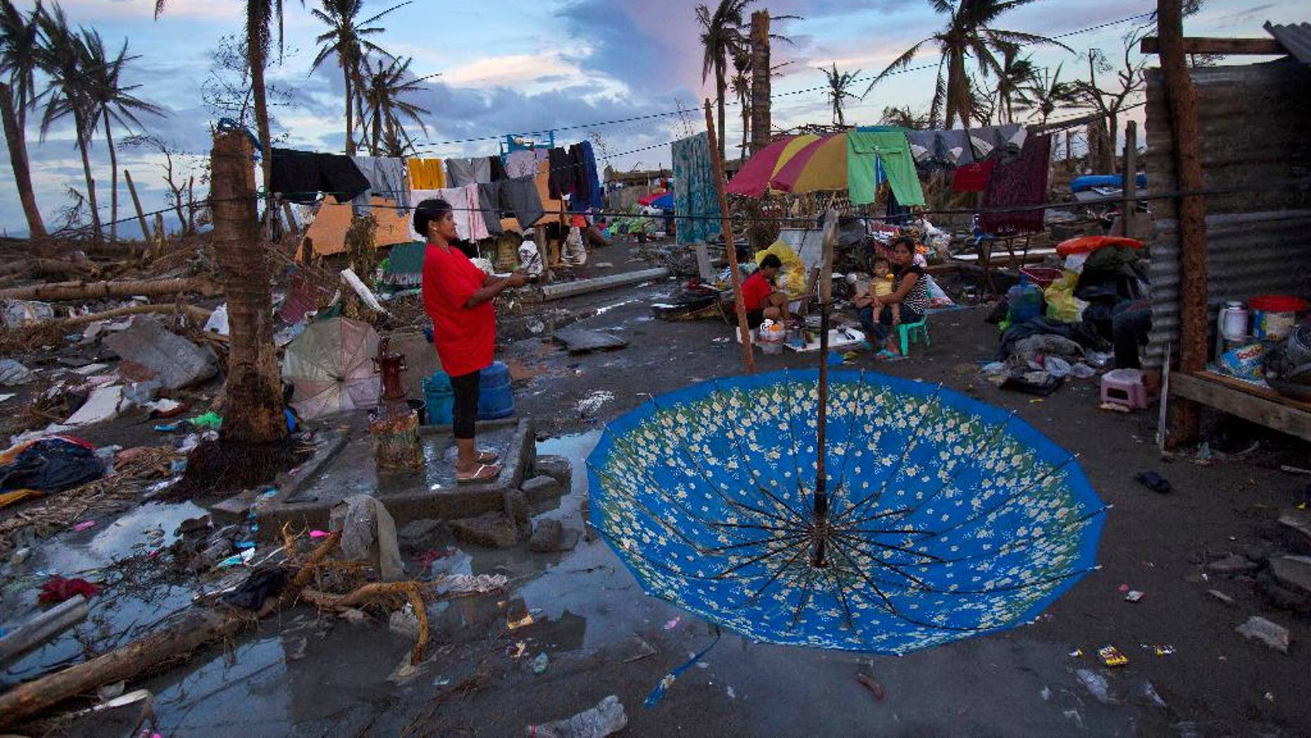 FILE - In this Nov. 13, 2013 file photo, Typhoon Haiyan survivors make camp in the ruins of their neighborhood on the outskirts of Tacloban, central Philippines. The Asian Development Bank says climate change has been making the poor in the Asia-Pacific region even poorer and is also setting back efforts to haul them out of poverty. According to the Manila-based lender, 1.5 million Filipinos have been pushed deeper into poverty and about 6 million lost their jobs in 2013 as a result of Typhoon Haiyan, one of the world's most powerful storms. (AP Photo/David Guttenfelder, File)