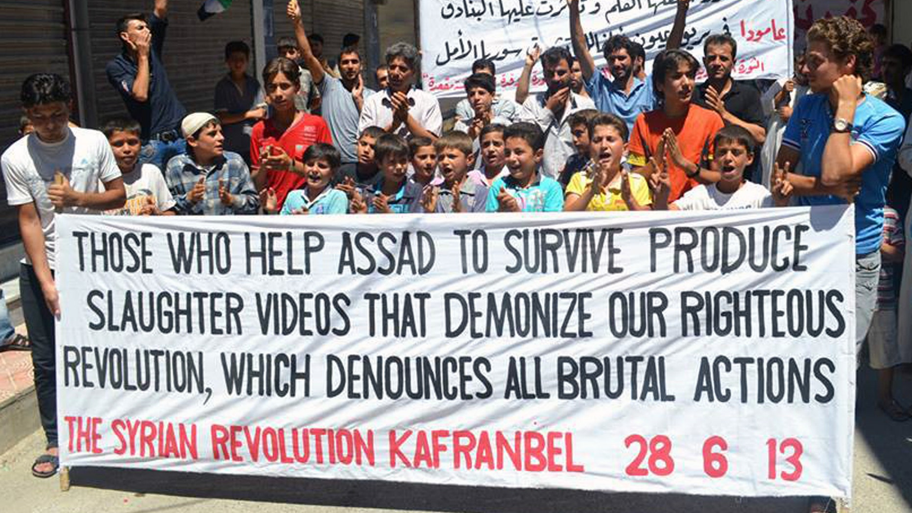 June 28, 2013: This citizen journalism image provided by Edlib News Network, ENN, which has been authenticated based on its contents and other AP reporting, shows anti-Syrian regime protesters holding a banner at Kafr Nabil town in Idlib province, northern Syria.