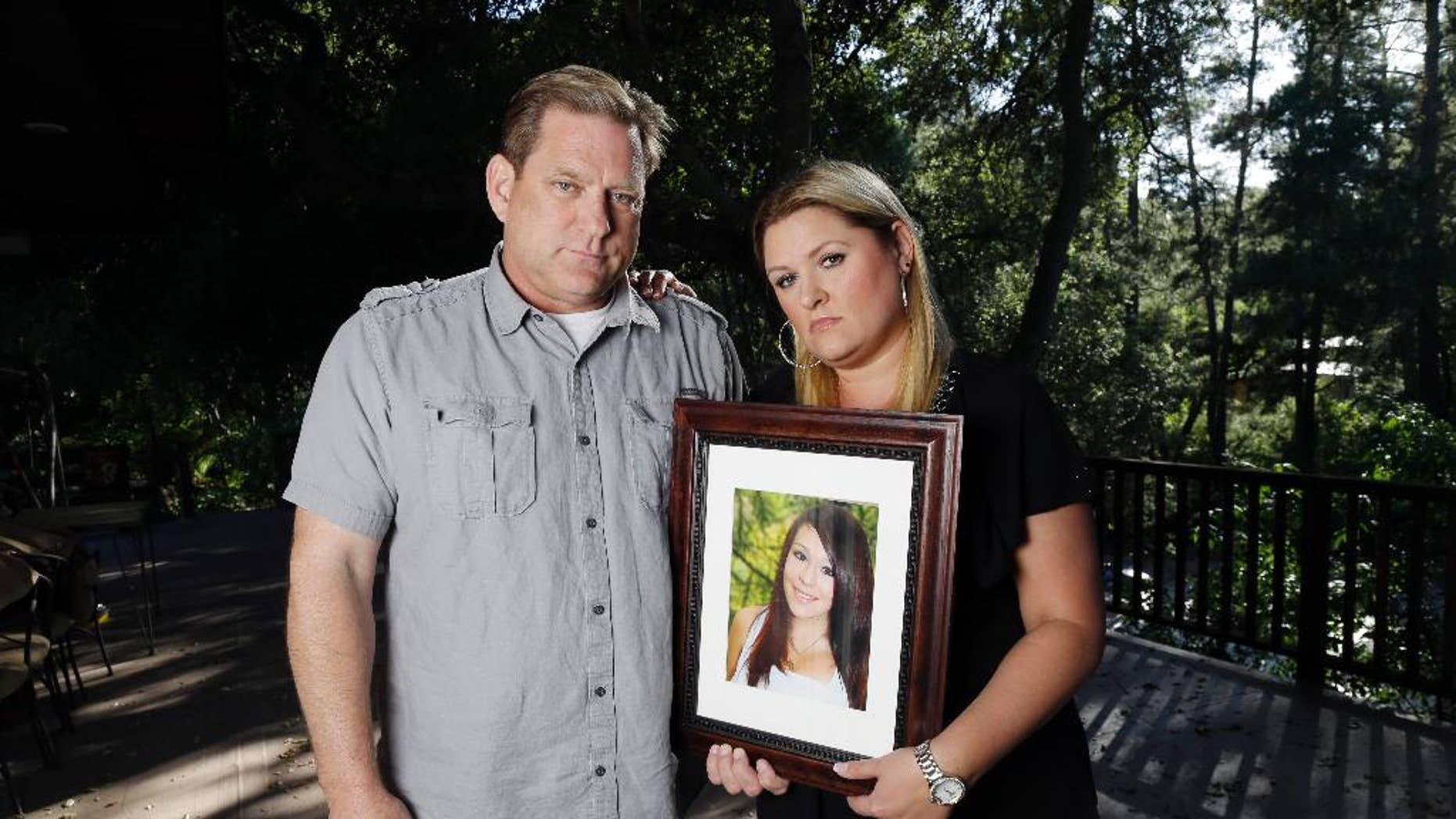 File - In this May 22, 2013 file photo, Larry Pott, left, and his wife Lisa pose for a portrait holding a picture of their daughter Audrie in Saratoga, Calif. Audrie Pott committed suicide in September 2012 after being sexually assaulted by three boys during a house party in Saratoga. (AP Photo/Marcio Jose Sanchez, file)