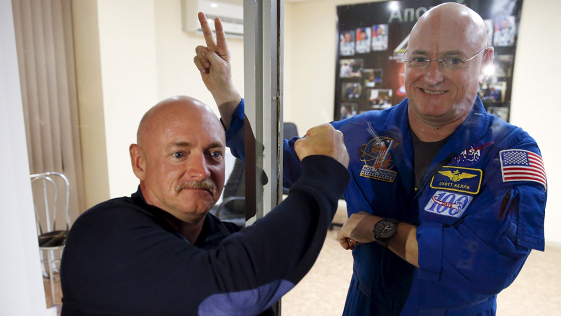 NASA astronaut Scott Kelly (R), member of the 43 International Space Station crew, and his twin brother Mark pose after a news conference at Baikonur cosmodrome March 26, 2015.