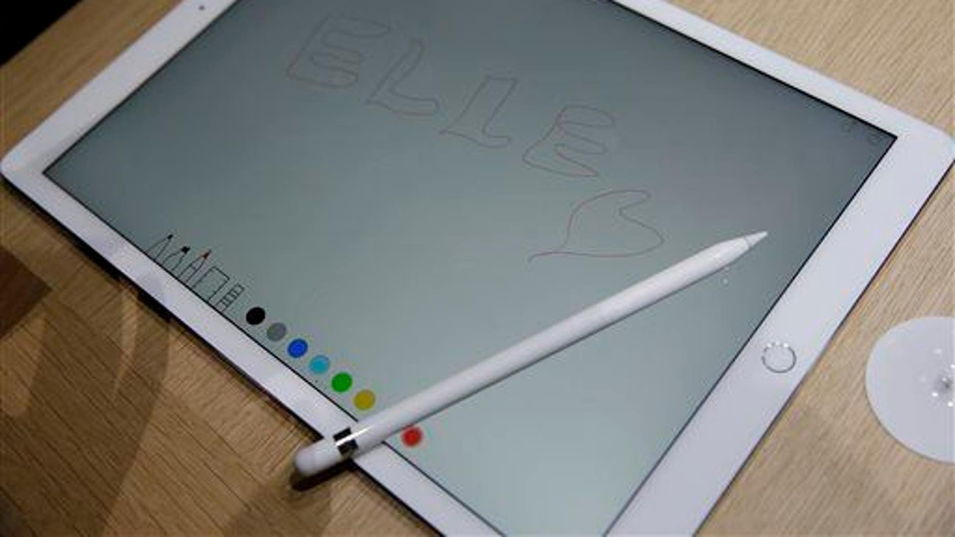 The new Apple Pencil rests on top of the iPad Pro.