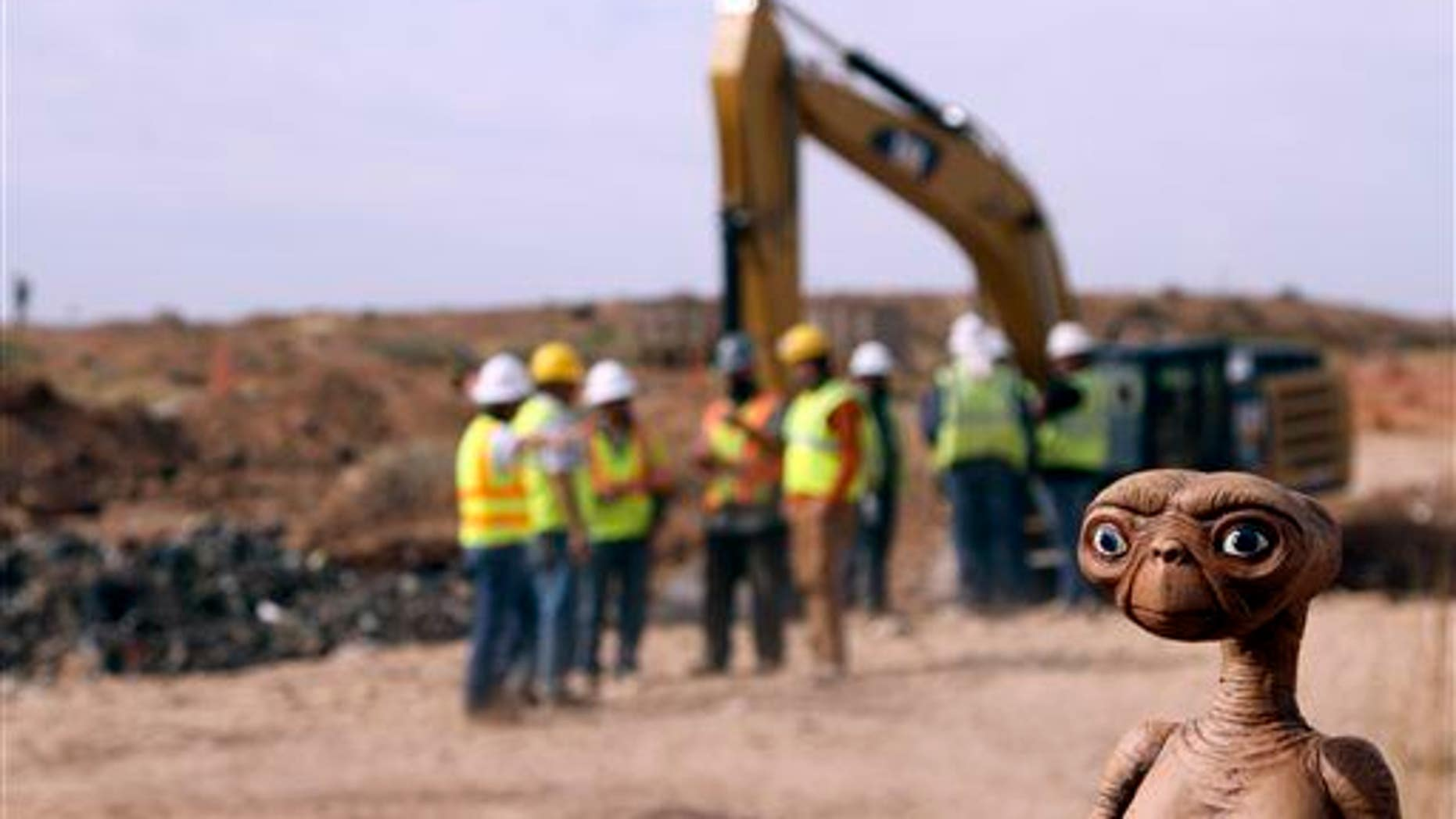 In this April 26, 2014, file photo, an E.T. doll is seen while construction workers prepare to dig into a landfill in Alamogordo, NM.