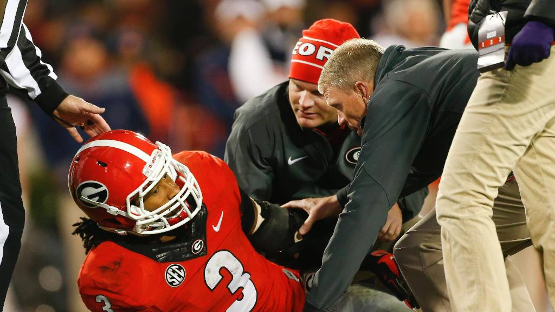 Members of the Georgia medical staff tend to injured running back Todd Gurley in the second half of an NCAA college football game  against Auburn Saturday, Nov. 15, 2014, in Athens, Ga. Georgia won 34-7. (AP Photo/John Bazemore)