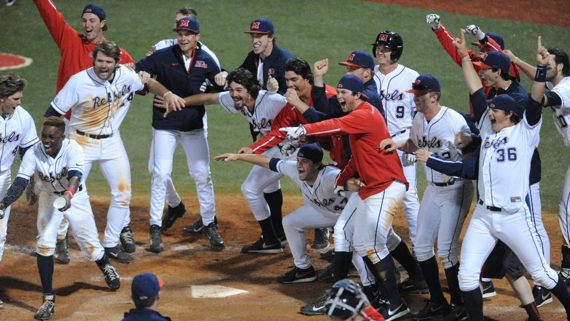 Mississippi players celebrate Austin Anderson's three-run walk-off home run in the 13th inning against Auburn in an NCAA college baseball game in Oxford, Miss., on Friday, April 4, 2014. Mississippi won 8-5. (AP Photo/Oxford Eagle, Bruce Newman) MANDATORY CREDIT  MAGS OUT  NO SALES