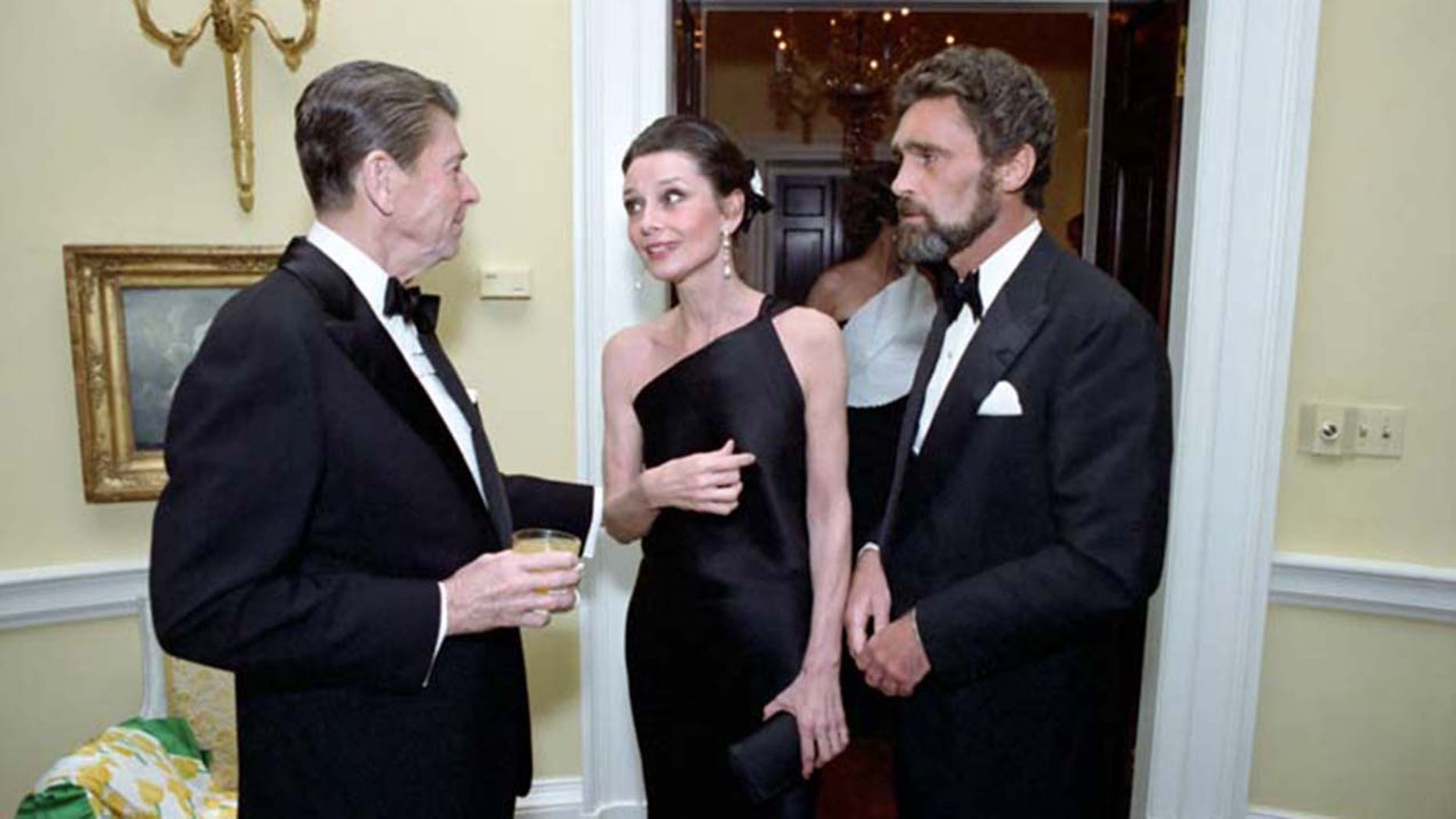 From left to right: President Ronald Reagan speaking with Audrey Hepburn and Robert Wolders.