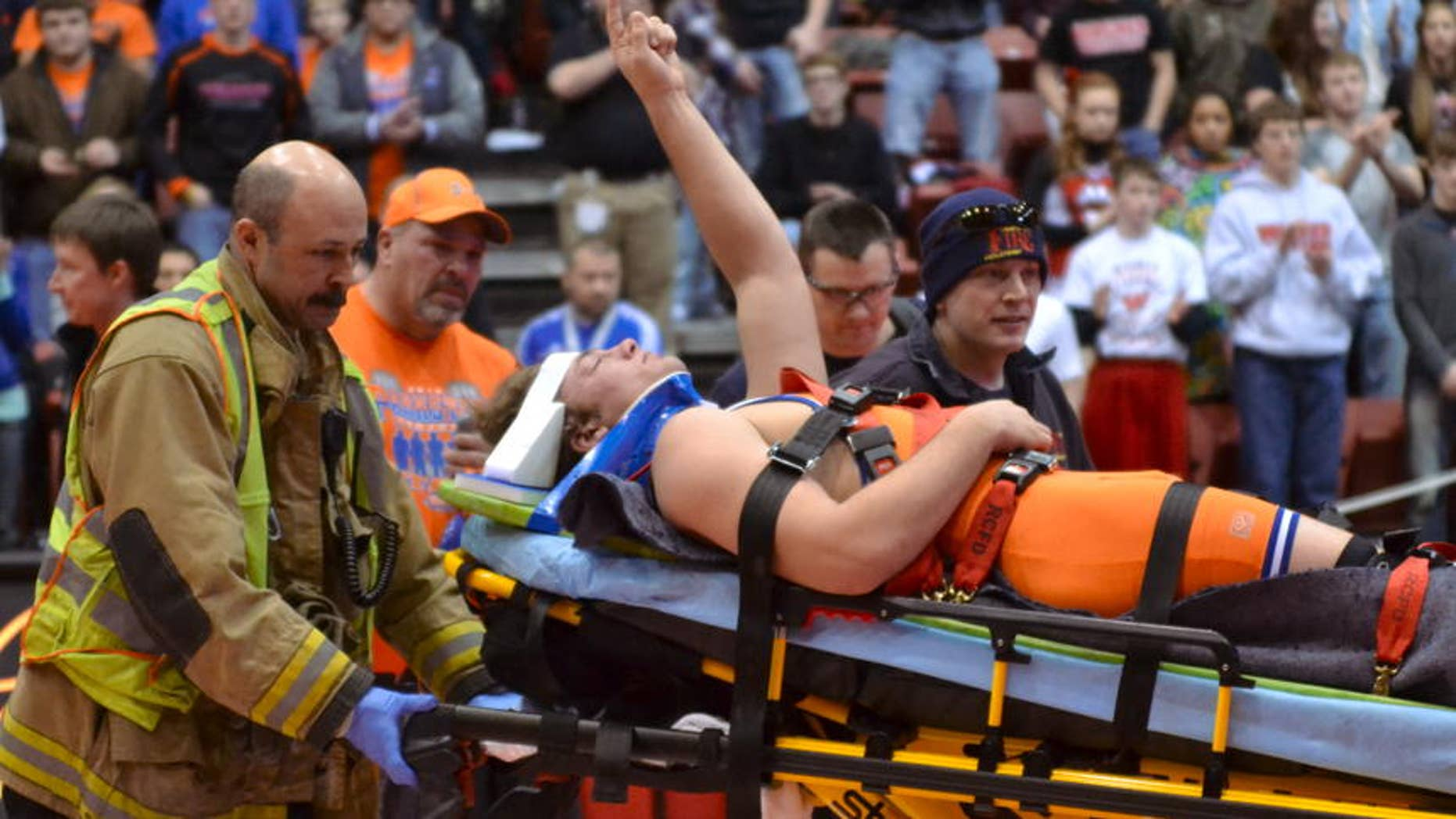 Parkston's Austin Bertram, center, is carried off the mat by medical personnel as he waves to the crowd giving him a standing ovation at the Class B state wrestling tournament on Saturday in Rapid City. (Garrick Hodge/Republic)
