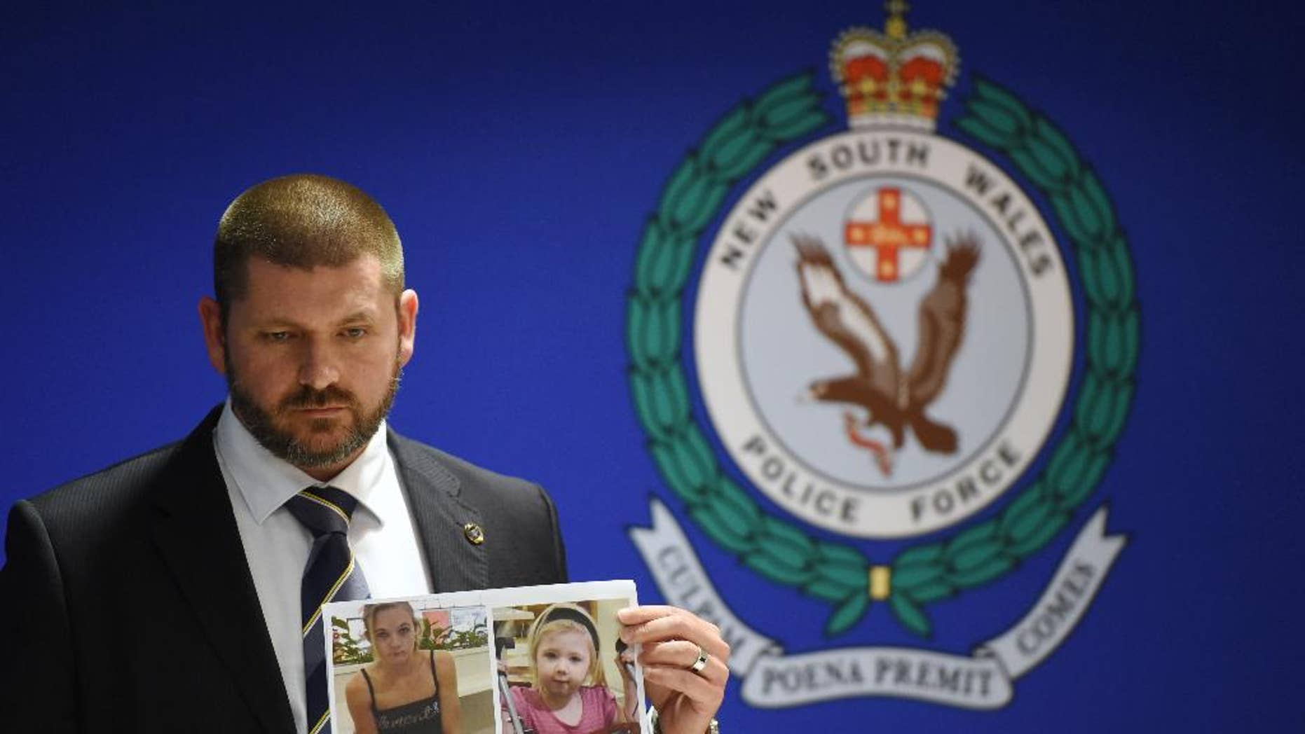 Police Detective Inspector Jason Dickinson holds up a photo of Karlie Jade Pearce-Stevenson and her daughter Khandalyce Kiara Pearce, during a press conference in Sydney, Wednesday, Oct. 21, 2015. A child whose decomposed body was found in a suitcase in southern Australia earlier this year is the daughter of a woman whose skeletal remains were found in 2010 in a forest 1,200 kilometers (750 miles) away, police said. (Dean Lewins/AAP Image via AP) NO ARCHIVING, AUSTRALIA OUT, NEW ZEALAND OUT, PAPUA NEW GUINEA OUT, SOUTH PACIFIC OUT