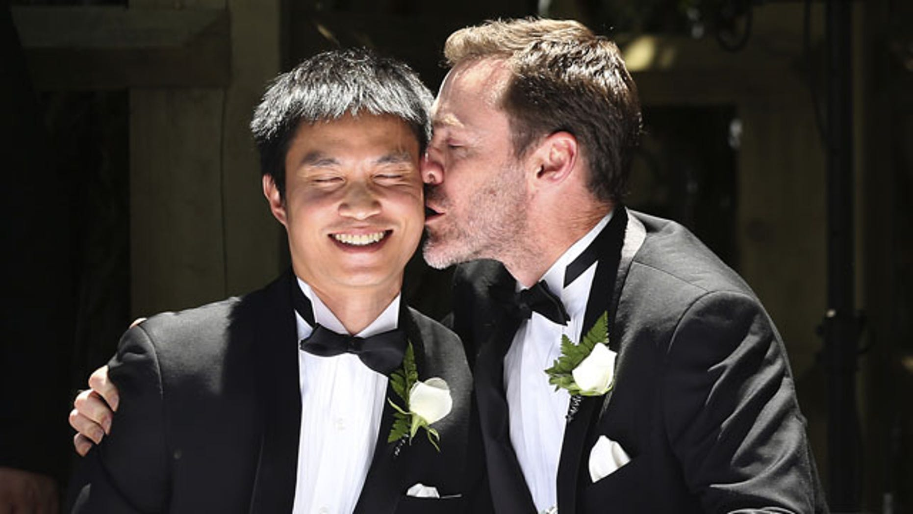 FILE - In this Dec. 7, 2013 file photo, Ivan Hinton, right, gives his partner Chris Teoh a kiss after taking their wedding vows during a ceremony at Old Parliament House in Canberra, Australia. Australia's highest court struck down a landmark law on Thursday, Dec. 12, 2013 that had begun allowing the country's first gay marriages. (AP Photo)