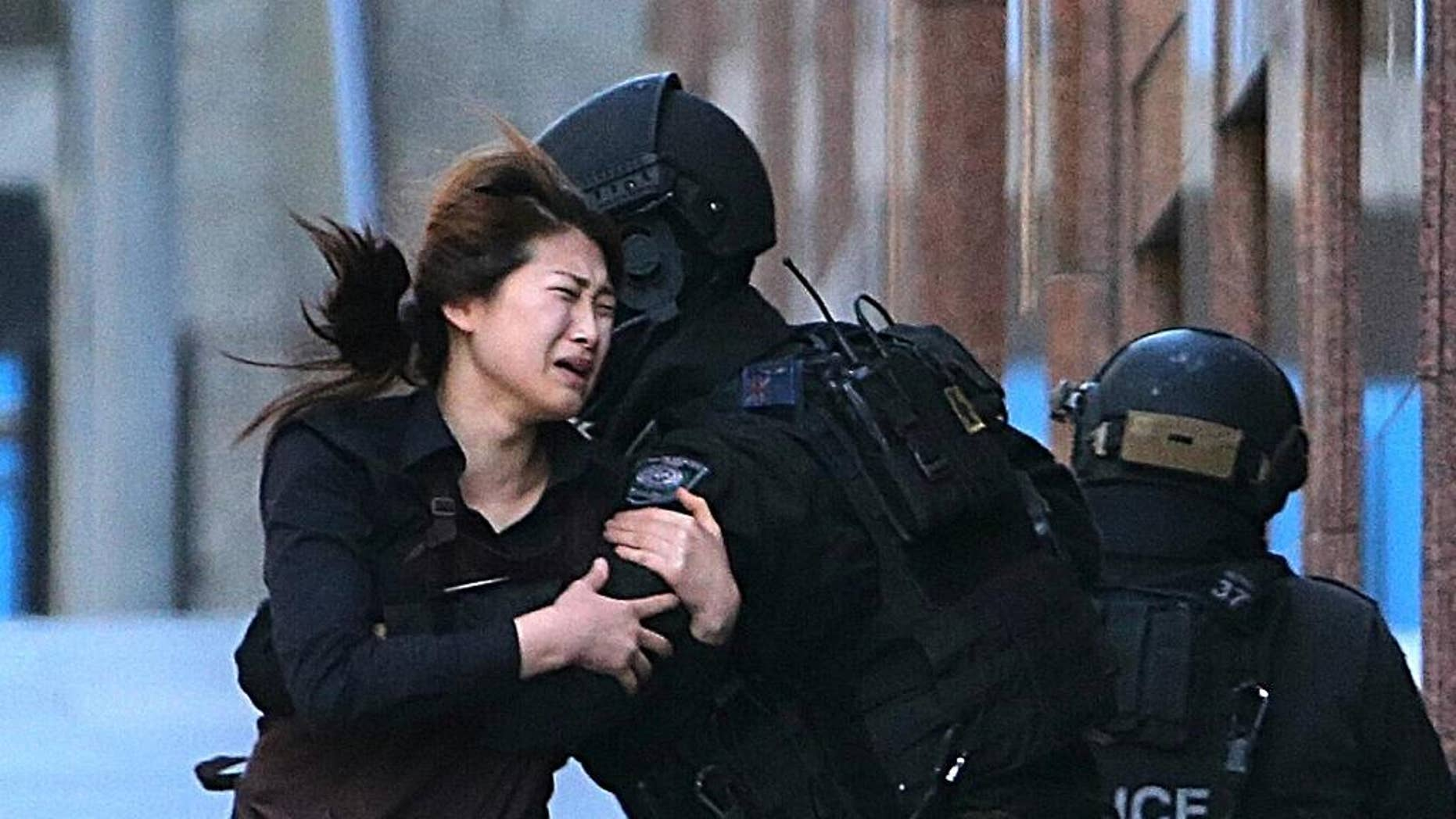 In this Dec. 15, 2014 file photo, a hostage runs to armed tactical response police officers for safety after she escaped from a cafe under siege at Martin Place in the central business district of Sydney, Australia.  For a country of just 24 million that is thousands of miles from Syria and Iraq, Australia has been unusually fertile ground for Islamic State recruiters.