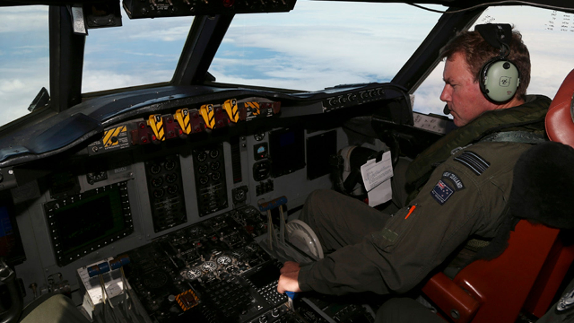 March 31, 2014: A Royal New Zealand Air Force  P-3 Orion's co-pilot and Squadron Leader Brett McKenzie controls the pane while  searching for the missing Malaysia Airlines Flight MH370 in the southern Indian Ocean. (AP Photo/Rob Griffith)