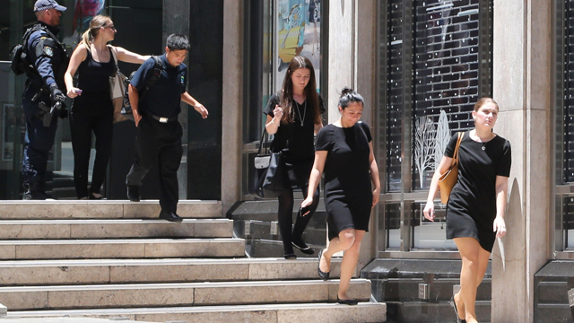December 15, 2014: Police evacuate people from an office building close to a cafe under siege at Martin Place in the central business district of Sydney, Australia. (AP Photo/Rob Griffith)