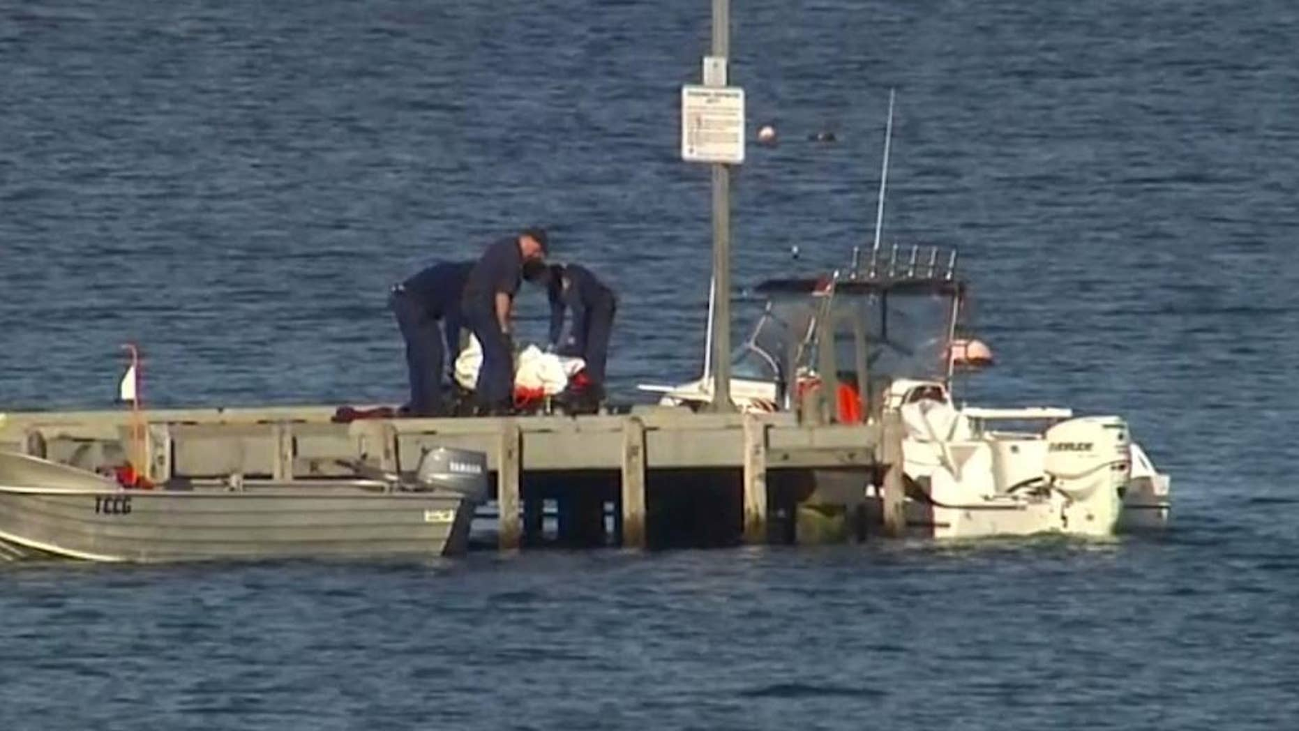 In this image taken from video, police carry a body in a bag and place it in on a stretcher on a jetty in Triabunna, off the Australian island state of Tasmania, on Saturday, July 25, 2015. A woman watched her father being mauled to death by a large shark on Saturday while the pair were diving, police said. (AuBC via AP)AUSTRALIA OUT
