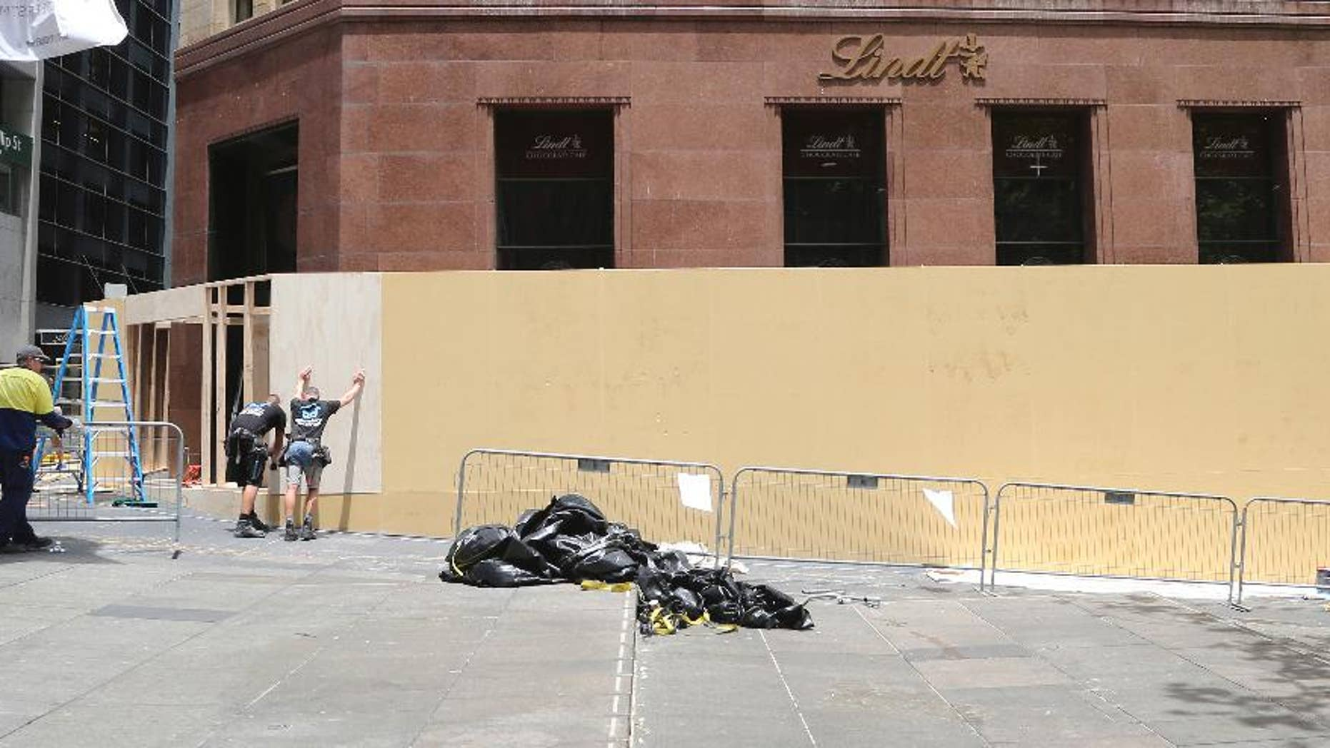 Dec. 23, 2014: Workers board up the Lindt Cafe in Martin Place in Sydney, Australia. Three people, including a gunman, were killed after police ended a siege in the central business district coffee shop in Sydney on Dec. 16. (AP Photo/Rob Griffith)