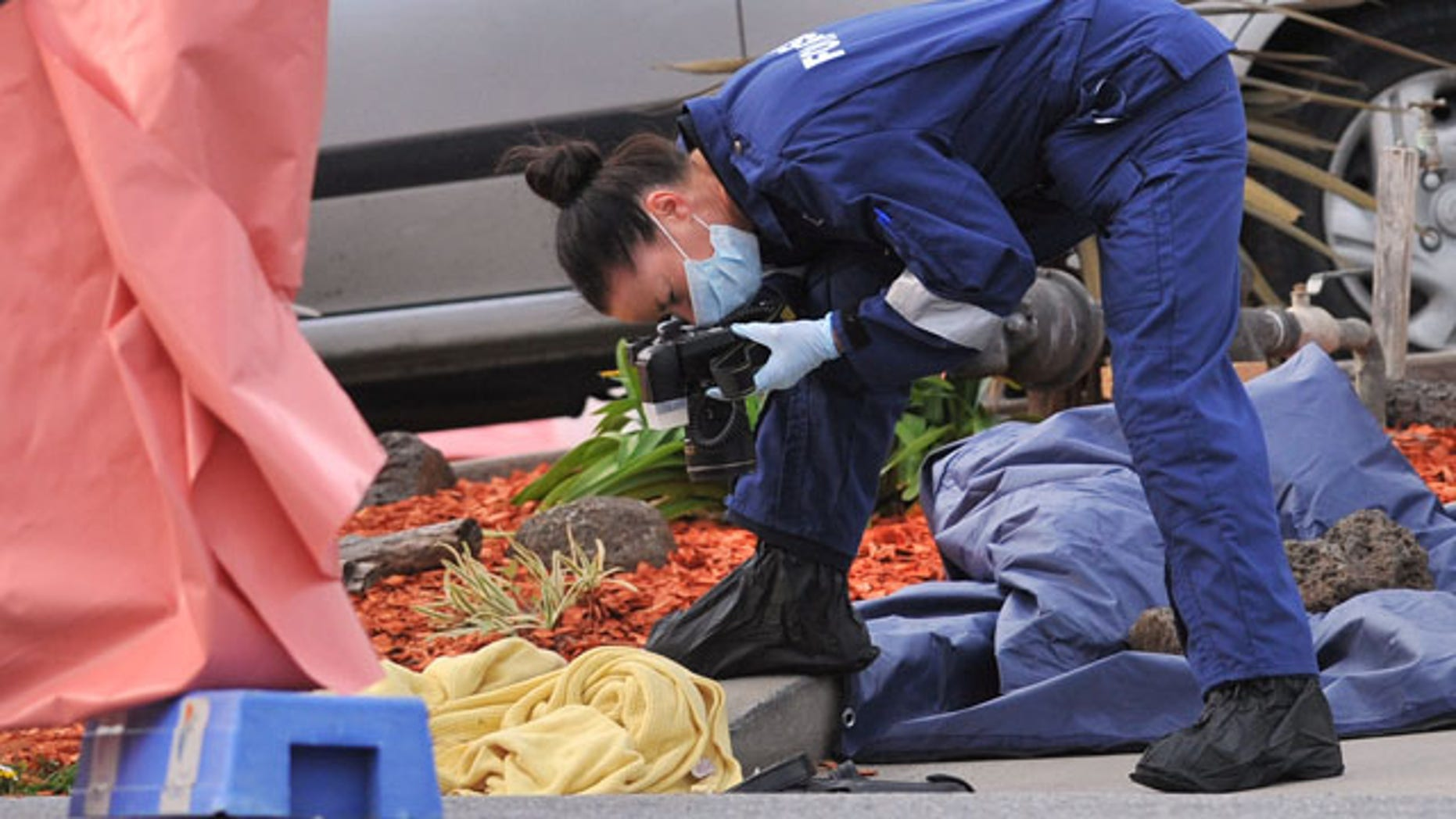 September 24, 2014: A forensic officer documents objects including a blanket at the scene of a fatal shooting at Endeavour Hills Police Station in Melbourne. (AP Photo/AAP Image, Julian Smith)