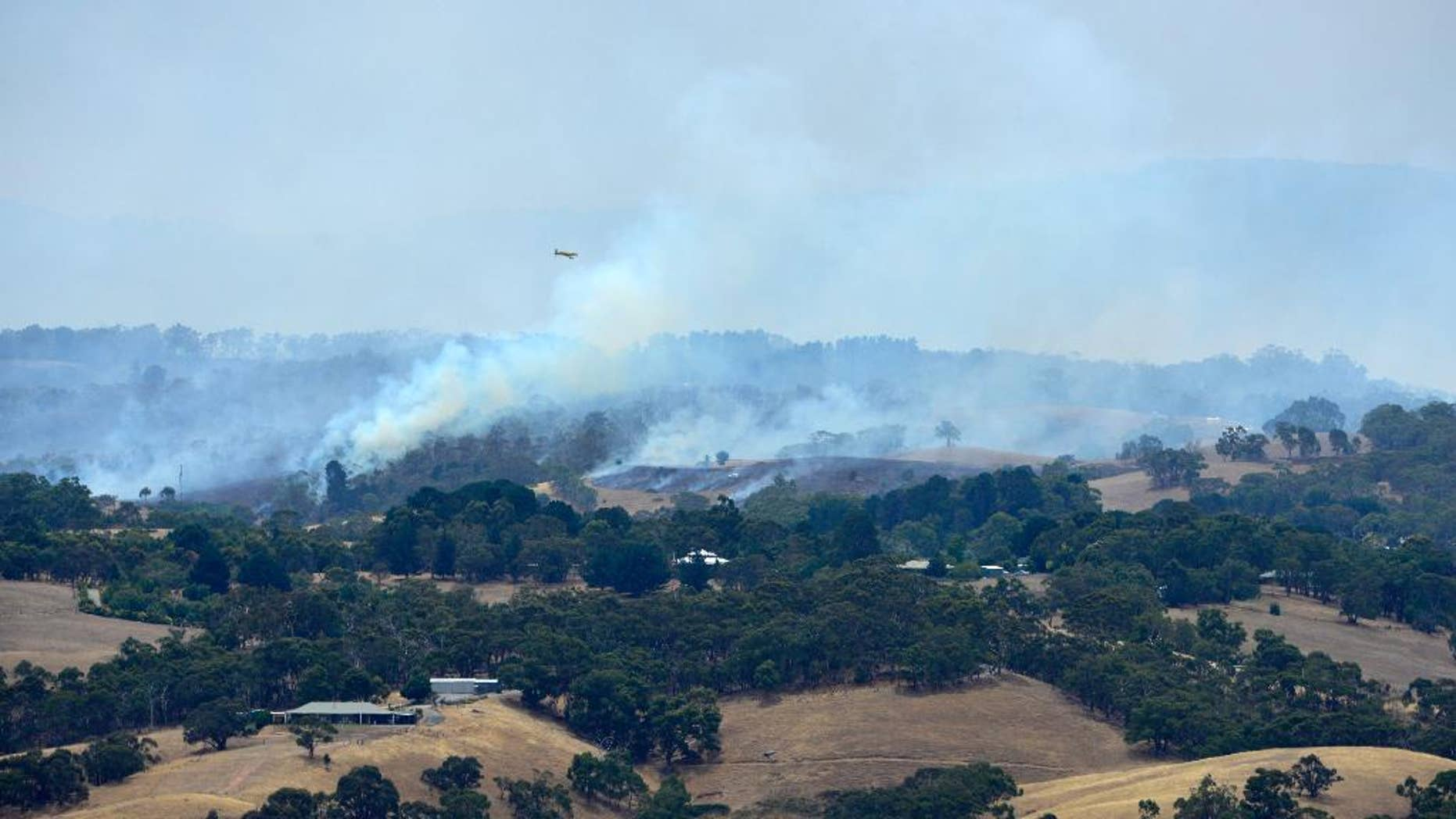 A plane flies over smoke from fires burring across the Adelaide Hills, near Adelaide, Australia, Saturday, Jan. 3, 2015.  Thousands of Australians fled their homes as wildfires raged across the nation's south on Saturday, with firefighters struggling to contain the blazes as strong winds fanned the flames. (AAP IMAGE/ DAVID MARIUZ) EDITORIAL USE ONLY, AUSTRALIA OUT, NEW ZEALAND OUT, PAPUA NEW GUINEA OUT, SOUTH PACIFIC OUT, NO ARCHIVES