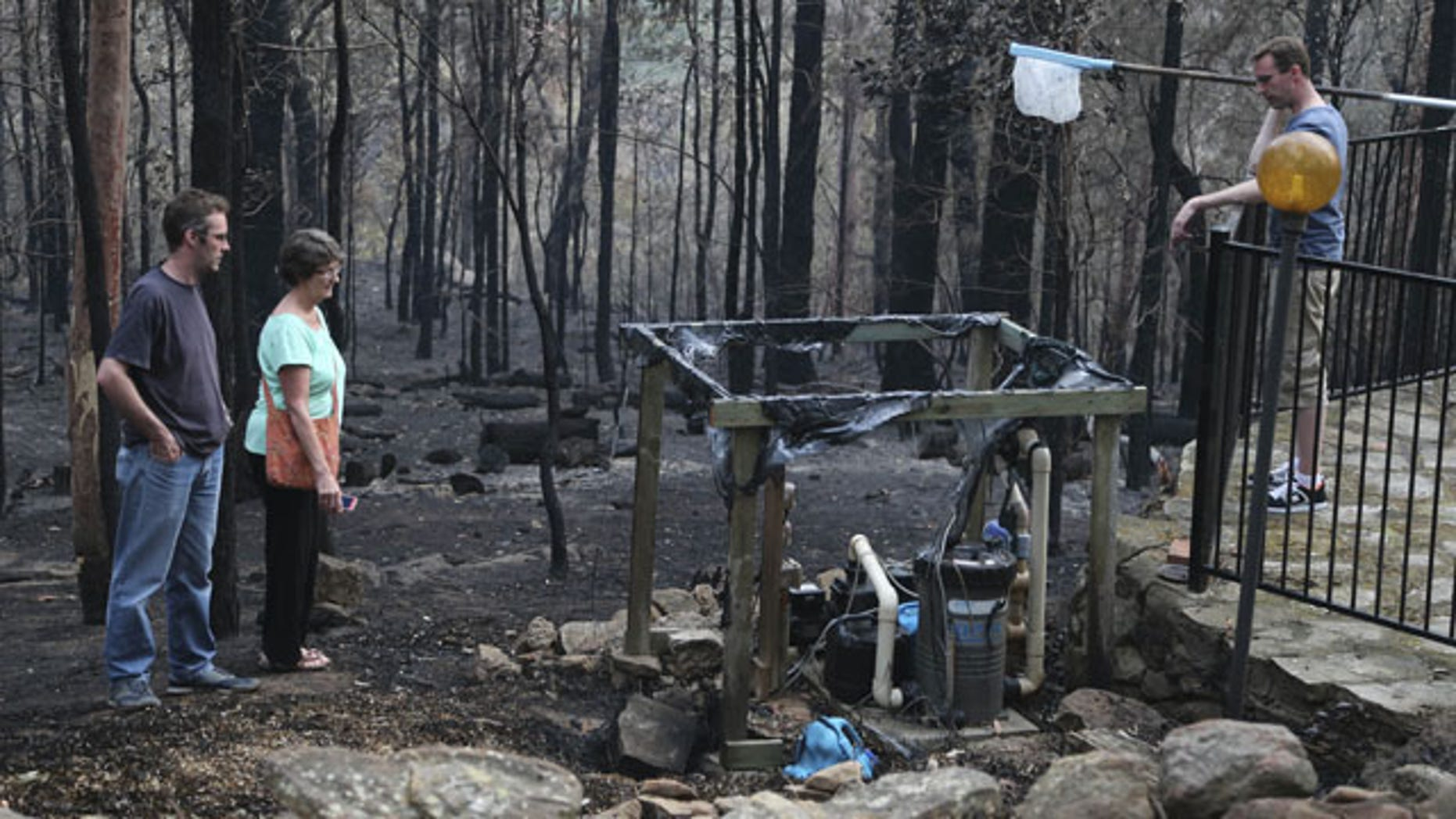 October 22, 2013: Jennifer Schweinsberg and her sons David left, and Adam, right, walk around the ruins of their family home in Sunny Ridge Drive in Winmalee 40 miles from Sydney in Australia after a wildfire swept through the street burning it and several other homes on Oct 18, 2013. (AP Photo)