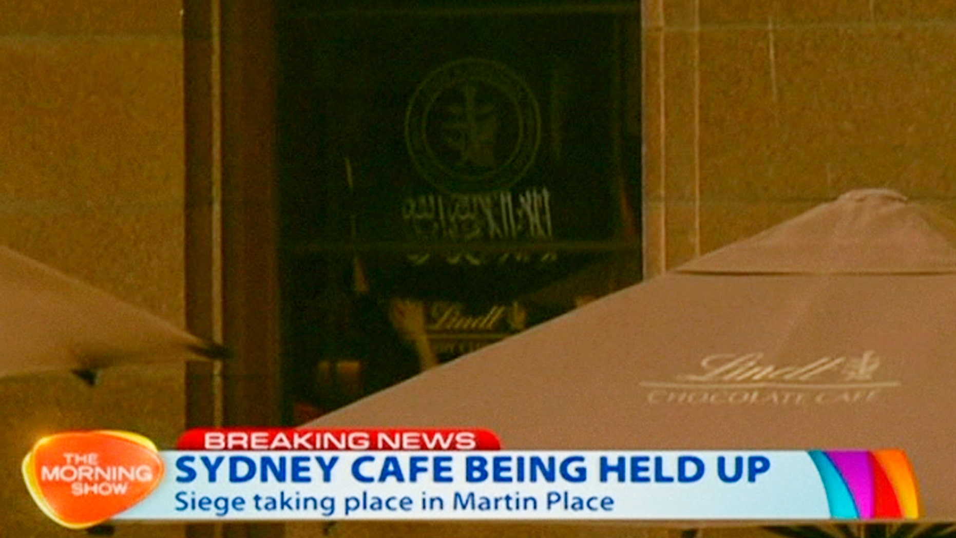 Dec. 15, 2014 - People holding up what appeared to be a black flag with white Arabic writing on it, inside a cafe in Sydney, Australia. A gunman took an unknown number of people hostage inside the downtown Sydney chocolate shop and cafe. The flag was  believed to contain an Islamic declaration of faith. (still taken from Ch.7 video)