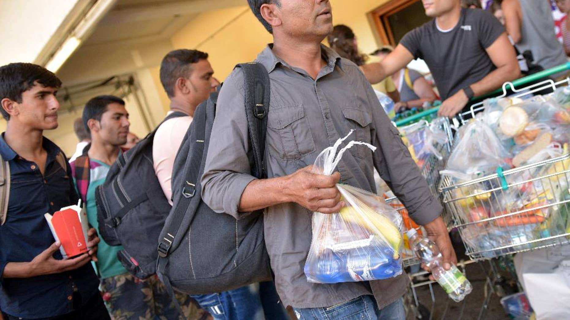 People receive food after they arrived at the Western railway station in Vienna, Austria, on Tuesday, Sept. 1, 2015. Some hundreds of migrants arrived by train from southern Europe, after making a perilous journey into Europe. (AP Photo/Hans Punz)