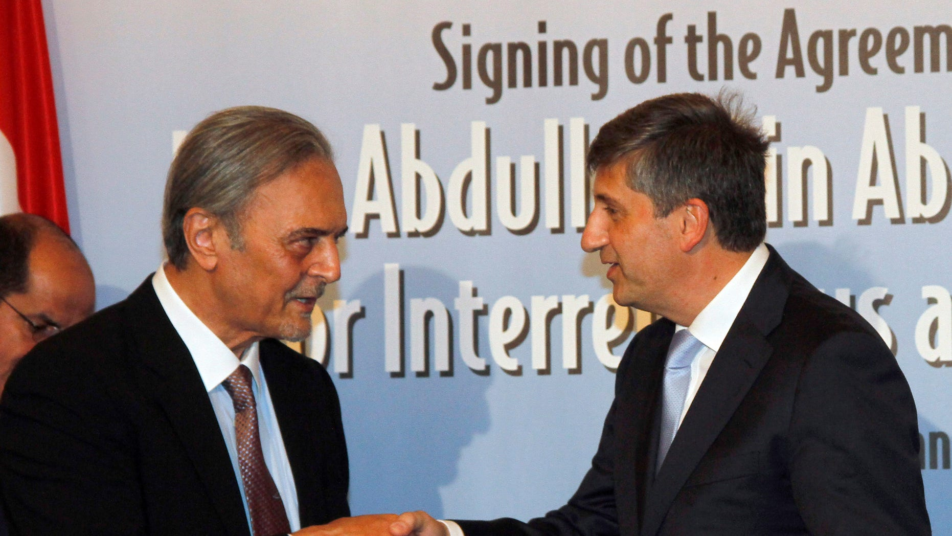 Saudi Arabia's Foreign Minister Prince Saud al-Faisal bin Abdulaziz Al Saud exchanges documents with his Austrian counterpart Michael Spindelegger, from left, after signing the agreement for the establishment of the King Abdullah Bin Abdulaziz International Center for Interreligious and Intercultural Dialogue, KAICID, in Vienna, Austria, Thursday, Oct. 13, 2011.