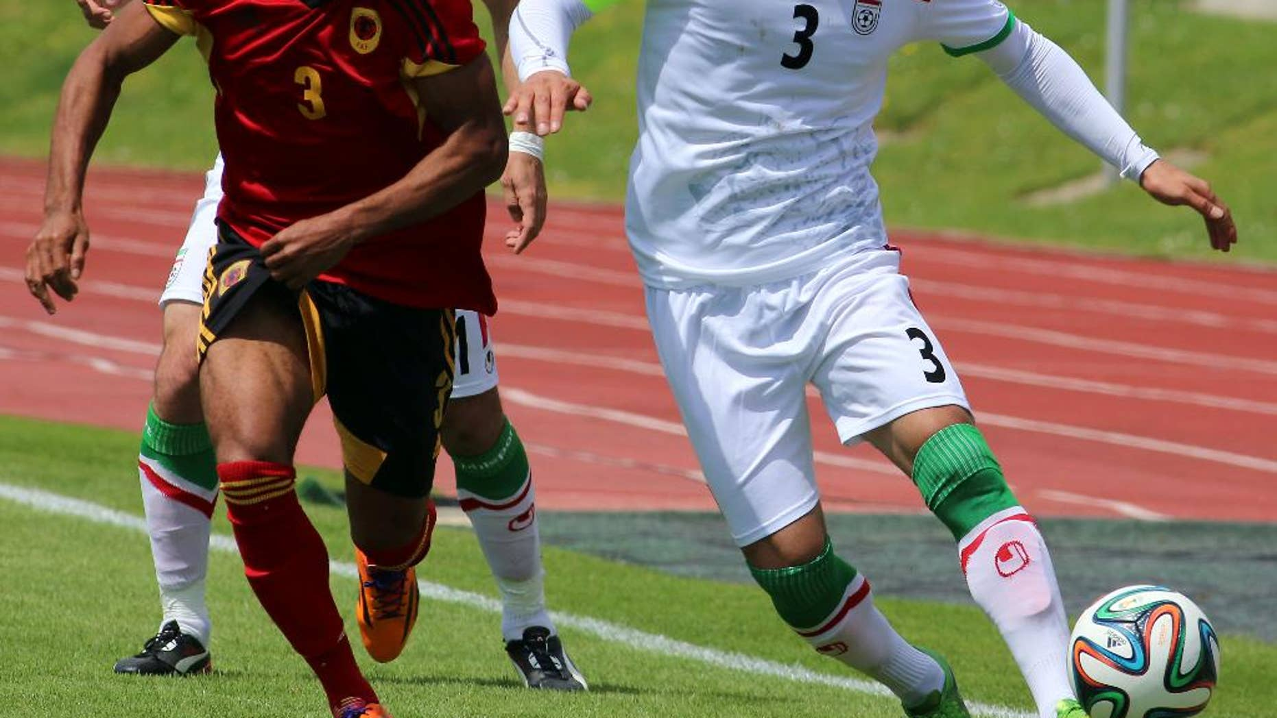 Iran's Ehsan Hajisafi, right, challenges for a ball with Lunguinha, left, of Angola during a friendly soccer match between Iran and Angola, in Hartberg, Austria, Friday, May 30, 2014. (AP Photo/Ronald Zak)