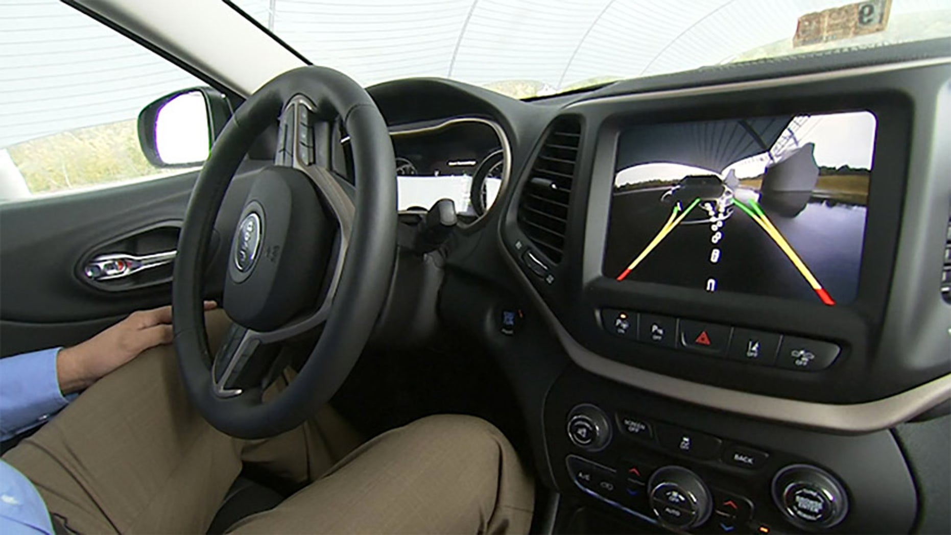 This image from video, taken Oct. 1, 2015, shows  Insurance Institute for Highway Safety (IIHS) Senior Research Engineer David Aylor in the drivers seat with an electronic display on the dashboard for parallel parking assistance at the IIHS Vehicle Research Center in Ruckersville, Va. American car buyers are baffled by a blizzard of new safety technologies in vehicles that vary from manufacturer to manufacturer, from model to model, and from one options package to another. (AP Photo/Dan Huff)