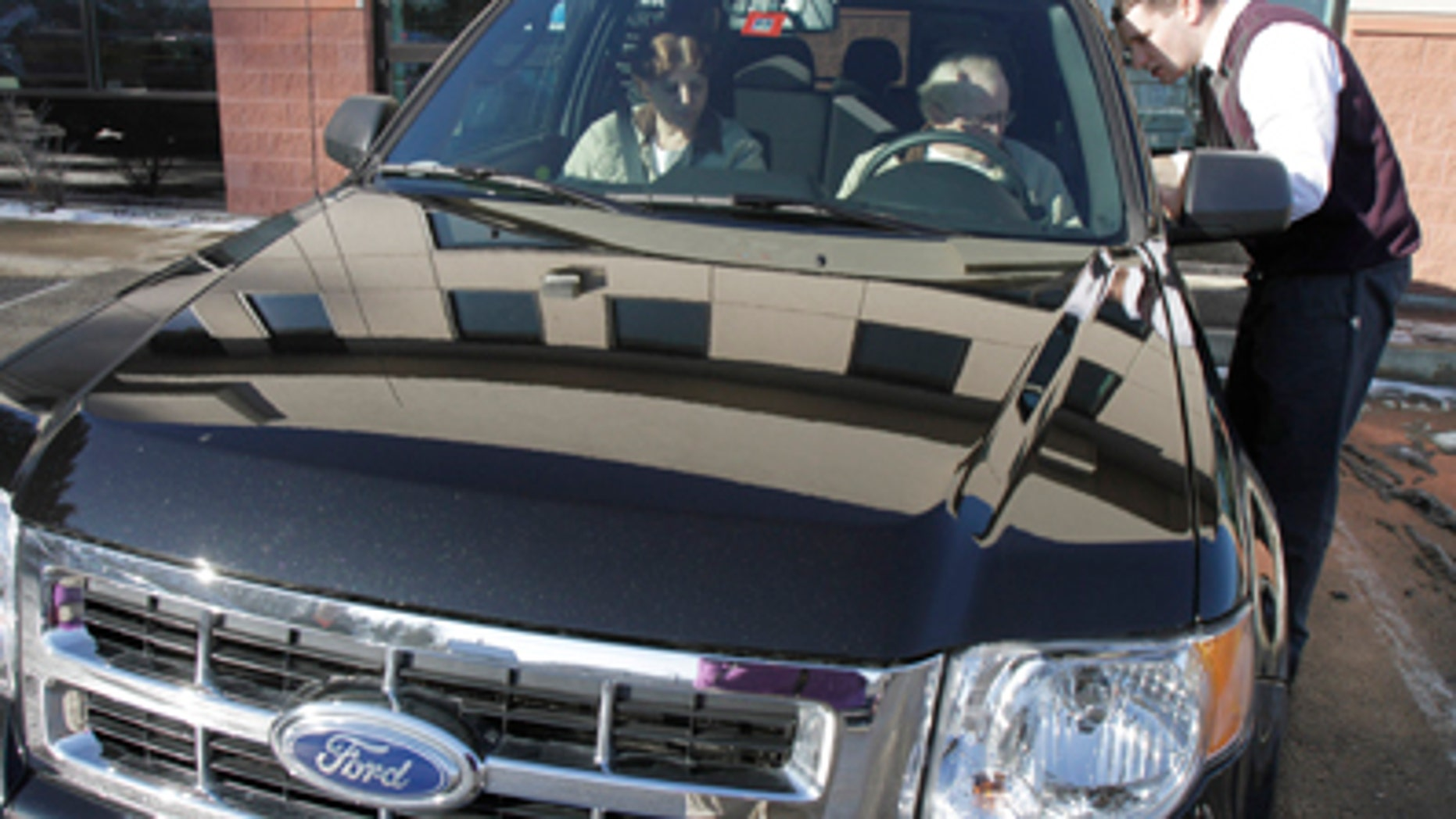 In this Dec. 30, 2010 photo, George and Sheila Snyder, of Washington, Vt., take delivery of their new 2011 Ford Escape from salesman John Cassel, right, at the Formula Ford dealership showroom in Montpelier, Vt. Automakers such as General Motors Co., Ford Motor Co. and Toyota Motor Corp. will report December and year-end sales figures throughout the day, on Tuesday, Jan. 4, 2011. Analysts are forecasting a modest increase that could show that customers bought more vehicles in 2010 than in 2009, when sales plummeted to their lowest levels since 1982. (AP Photo/Toby Talbot)