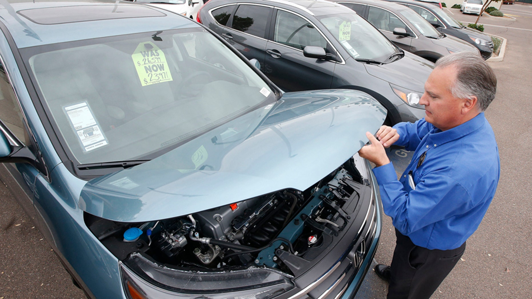 FILE - In this Dec. 2, 2014, file photo, Mike Johnson, a sales manager at a Honda car dealership, opens the hood of a Honda CRV SUV, in Tempe, Ariz. Automakers release vehicle sales for June 2015 on Wednesday, July 1, 2015. (AP Photo/Ross D. Franklin, File)