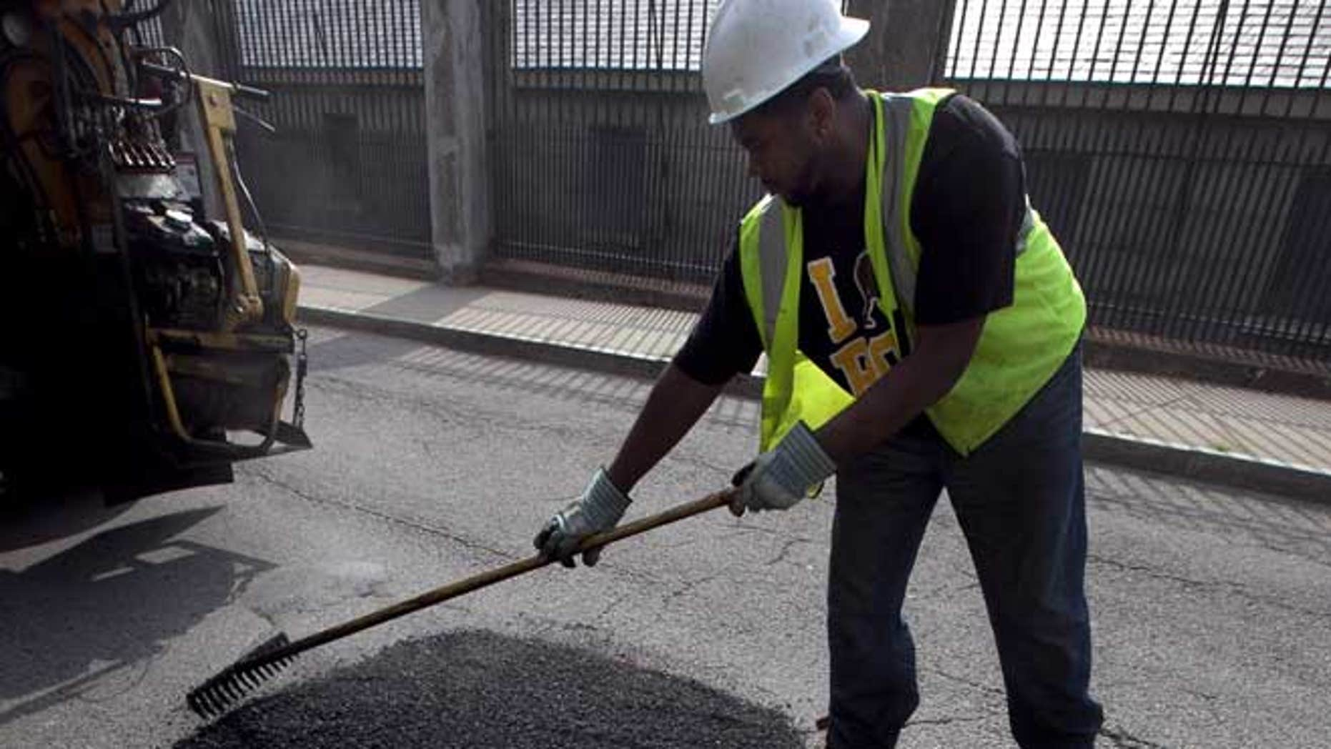In this Thursday, July 19, 2012 photo Boston Public Works worker Tyrone Odom, of Boston, fills a pothole with asphalt in Boston's Charlestown neighborhood.