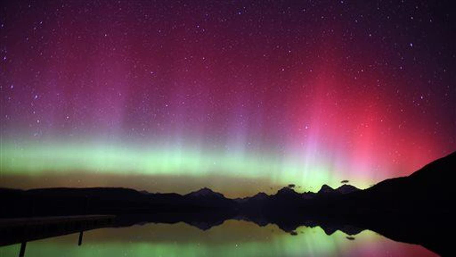 In this April 9, 2015, photo, an aurora borealis illuminates the night sky over Lake McDonald in Glacier National Park, Mont.