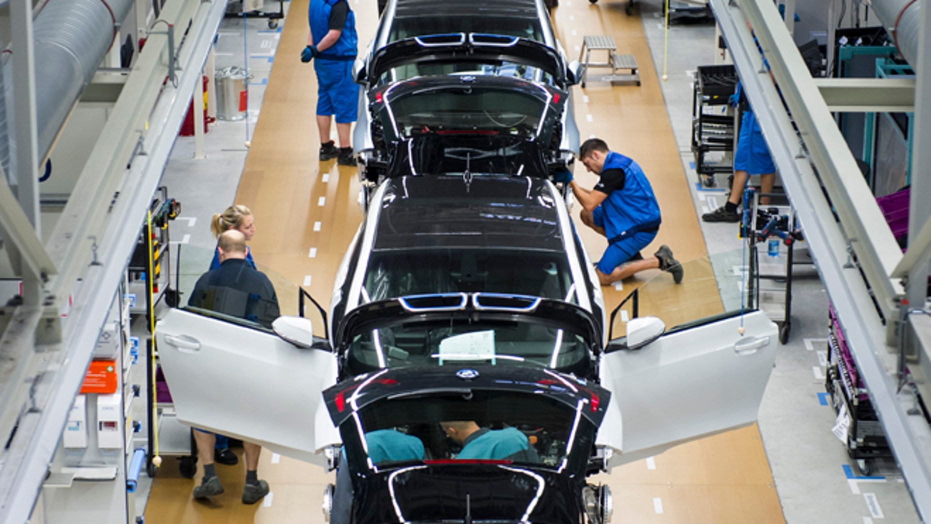 LEIPZIG, GERMANY - SEPTEMBER 18:  Workers assemble a new BMW i3 electric car on the assembly line at the BMW factory on September 18, 2013 in Leipzig, Germany. The i3 is BMW's first mass market electric car and the company has invested EUR 400 million into its production at the Leipzig factory. (Photo by Jens Schlueter/Getty Images)