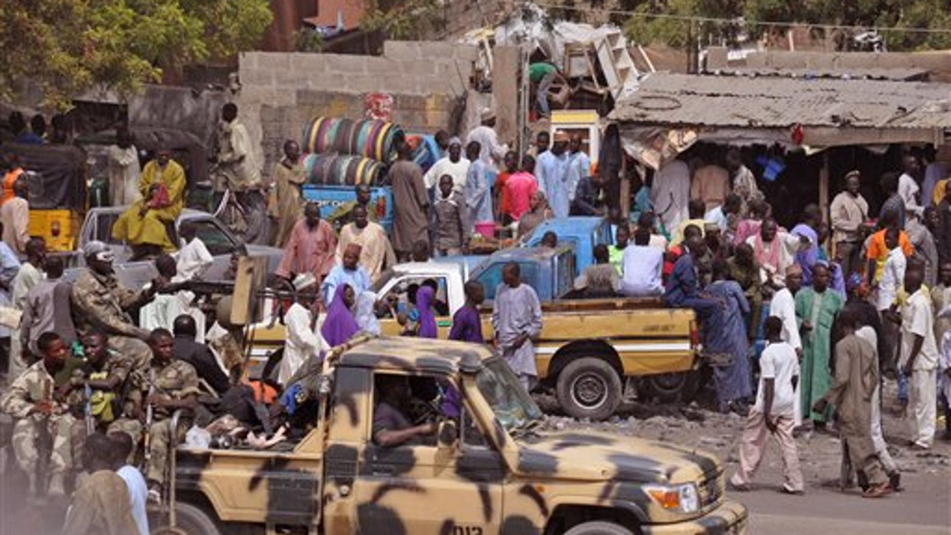 FILE - In this file photo taken Tuesday, Jan. 27, 2015,  Nigerian soldiers, left, pass by on the back of an armed truck as they patrol a local market after . Nigerian jets bomb Boko Haram out of a slew of northeastern Nigerian towns and villages.  (AP Photo/Jossy Ola, File)