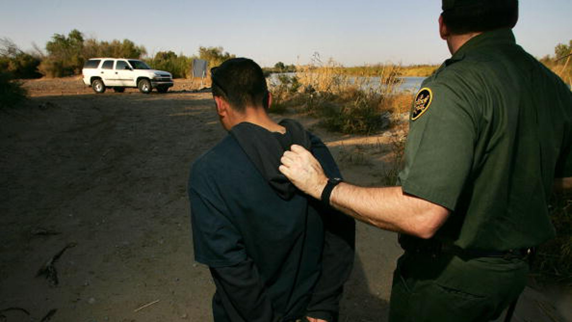 YUMA, AZ - MARCH 17:  U.S. Customs and Border Protection border patrol agent Ben Vik apprehends a suspected illegal immigrant on the California side of the Colorado River on March 17, 2006 near Yuma, Arizona. As Congress begins a new battle over immigration policy, U.S. Customs and Border Protection (CBP) border patrol agents in Arizona are struggling to control undocumented immigrants that were pushed into the region by the 1990?s border crack-down in California called Operation Gatekeeper. A recent study by the Pew Hispanic Center using Census Bureau data estimates that the United States currently has an illegal immigrant population of 11.5 million to 12 million, about one-third of them arriving within the past 10 years. More than half are from Mexico. Ironically, beefed-up border patrols and increased security are reportedly having the unintended result of deterring many from returning to their country of origin.  (Photo by David McNew/Getty Images)