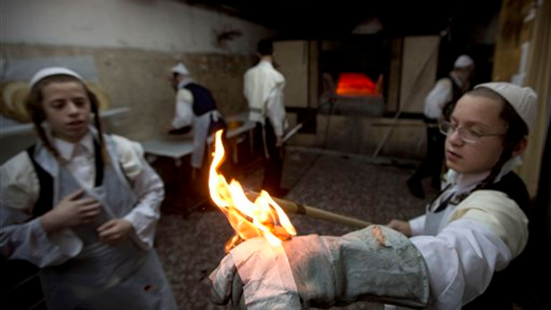 Ultra-Orthodox Jews prepare special matzoh, a traditional handmade Passover unleavened bread, at a bakery in Jerusalem, Wednesday, April 1, 2015. (AP Photo/Sebastian Scheiner)