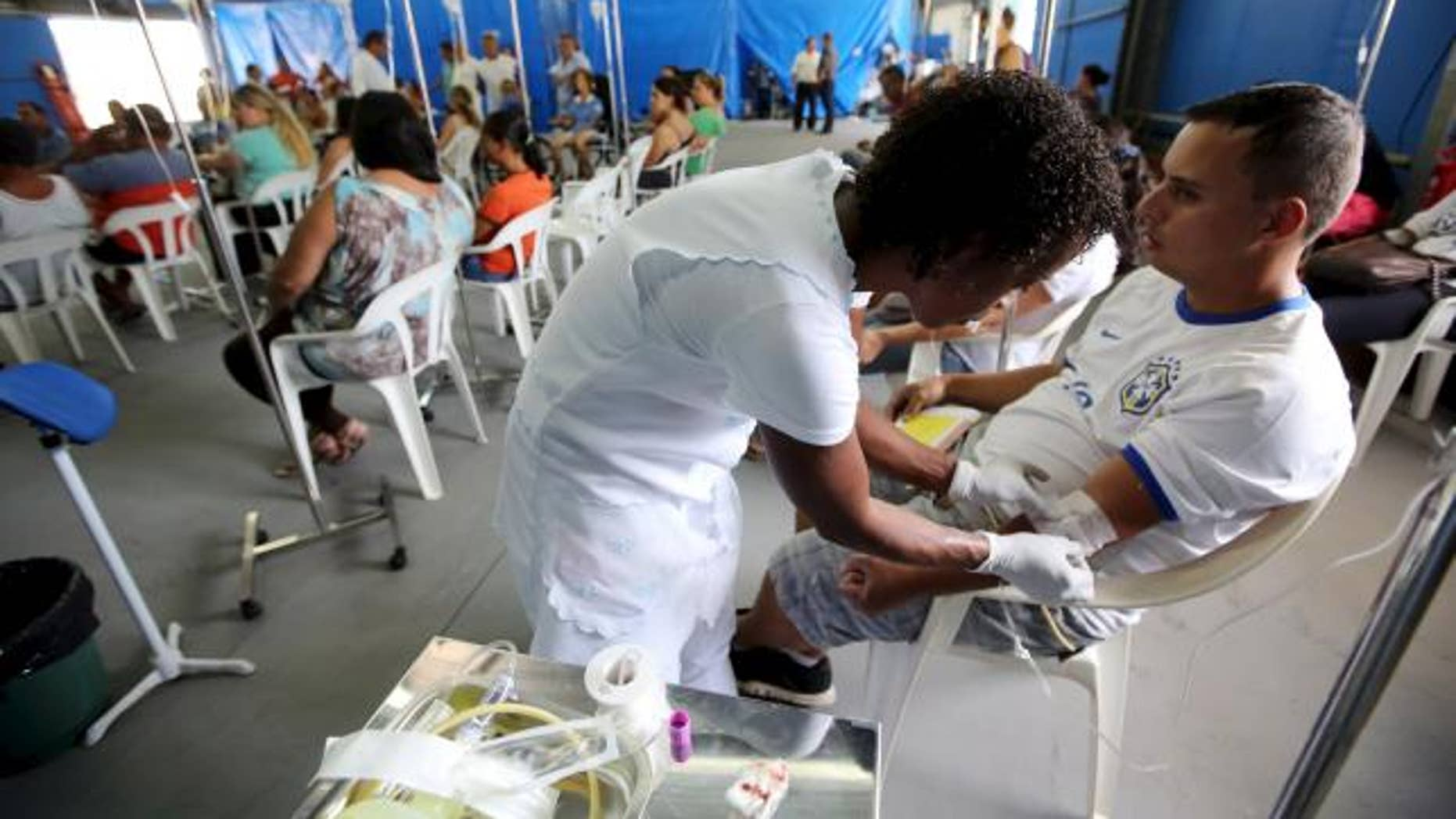 March 5, 2015: A patient is administered drips as he awaits the results of his dengue examination, in a medical tent in Rio Claro, Brazil.